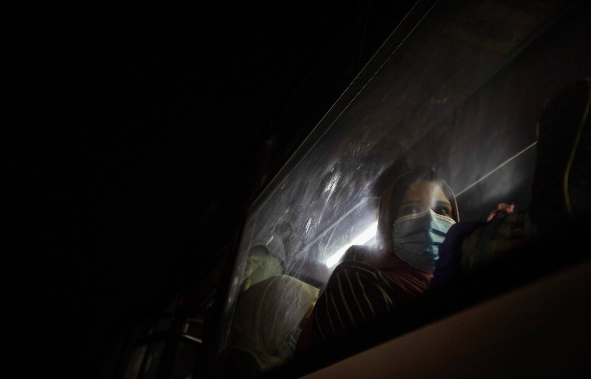 A Palestinian woman wearing a face mask to prevent the spread of the coronavirus waits in a bus in Gaza City to go to the Rafah border crossing into Egypt on Sept. 27, 2020. (AP Photo/Khalil Hamra)