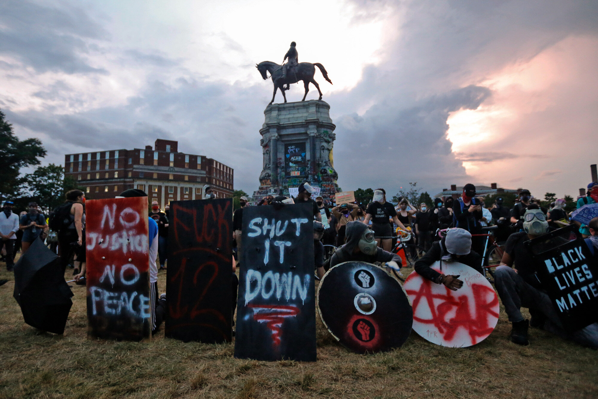 Protesters with shields and gas masks wait for police action as they surround the statue of Confederate Gen. Robert E. Lee on Monument Avenue in Richmond, Va., on June 23, 2020. The state ordered the area around the statue closed from sunset to sunrise, but the protesters had no plans to disperse. (AP Photo/Steve Helber)