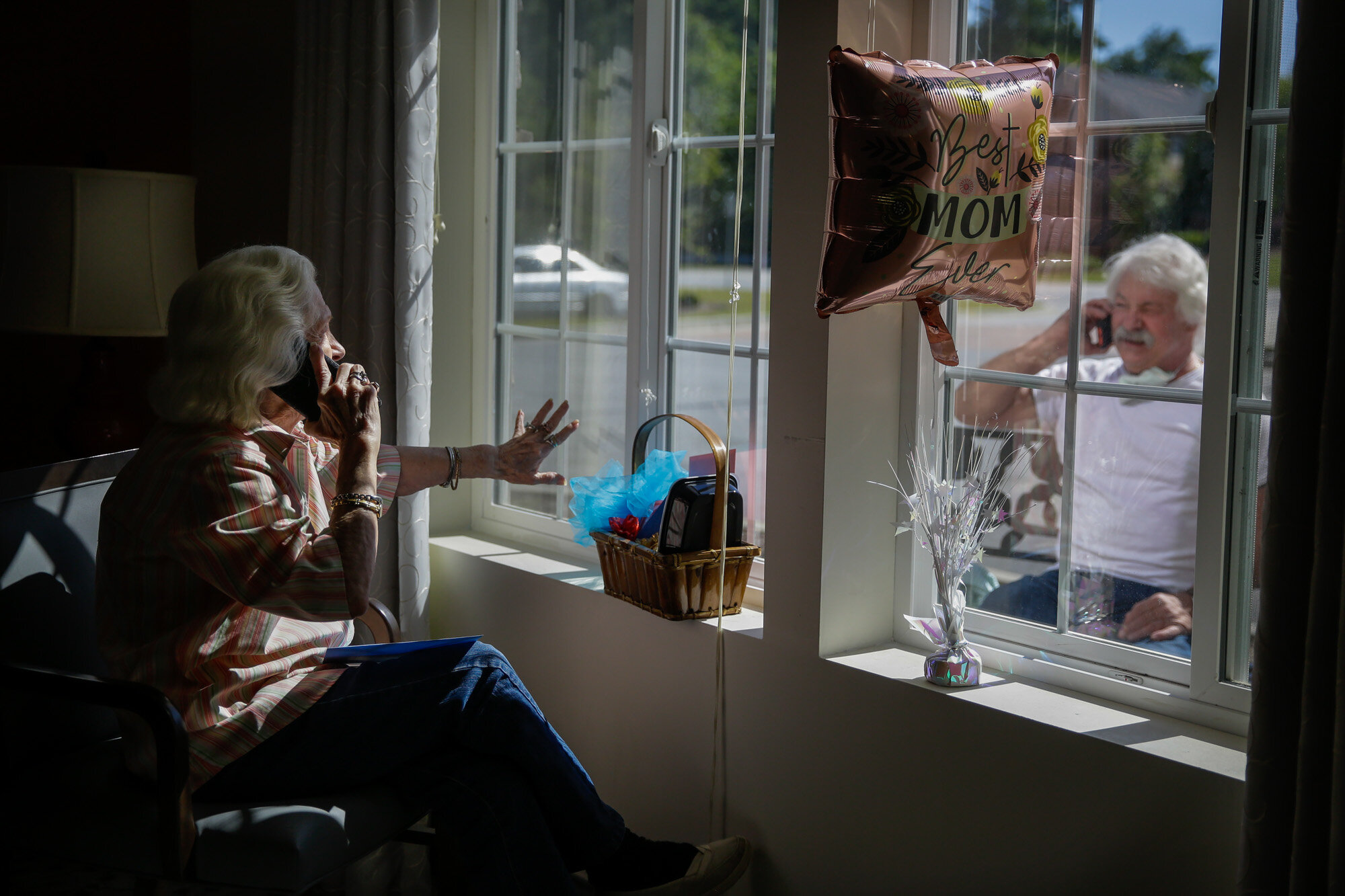 """Mary Faye Cochran, 86, sings """"You Are My Sunshine"""" over the phone to her son Stacey Smith through a window on Mother's Day, Sunday, May 10, 2020, at Provident Village at Creekside senior living in Smyrna, Ga. (AP Photo/Brynn Anderson)"""