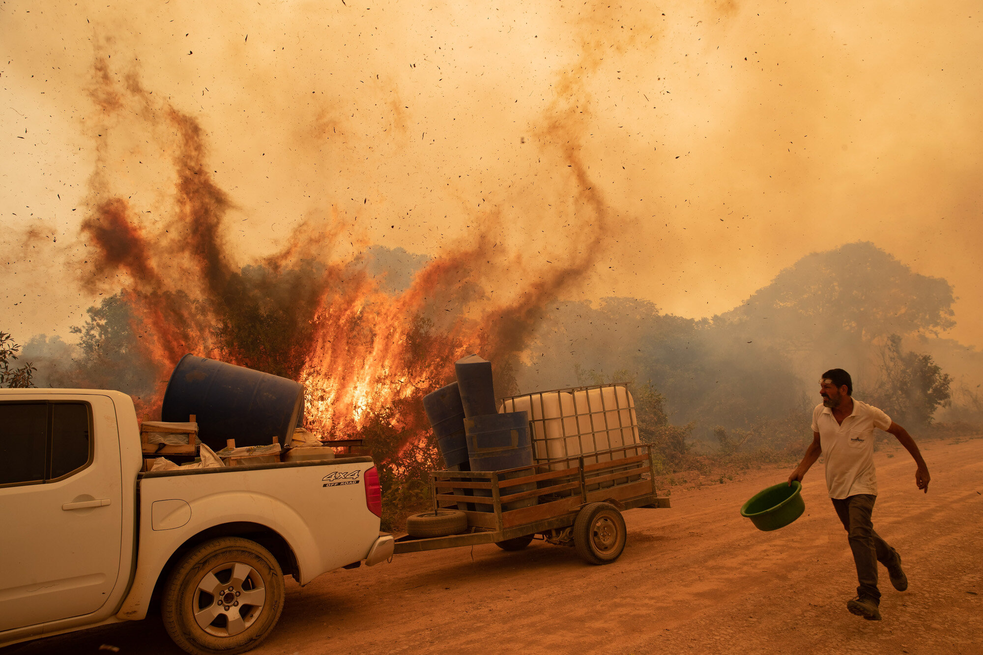 A volunteer tries to douse a fire on Transpantaneira road in the Pantanal wetlands near Pocone, Mato Grosso state, Brazil, on Sept. 11, 2020. The number of fires in Brazil's Pantanal, the world's biggest tropical wetlands, more than doubled in the first half of 2020 compared to the same period last year, according to data released by a state institute. (AP Photo/Andre Penner)