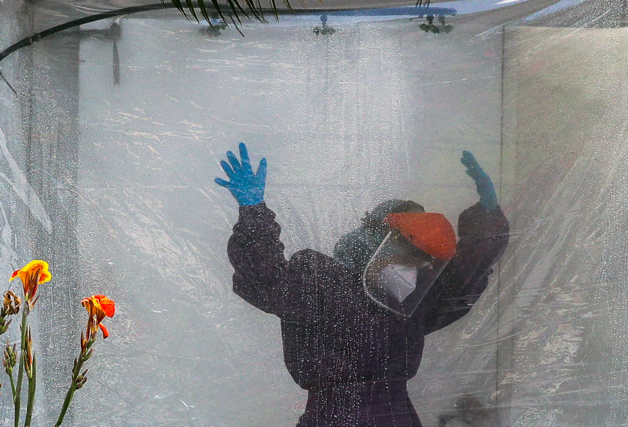 A health worker wearing a protective suit is disinfected in a portable tent outside the Gat Andres Bonifacio Memorial Medical Center in Manila, Philippines, on April 27, 2020, during an enhanced community quarantine to prevent the spread of the coronavirus. (AP Photo/Aaron Favila)