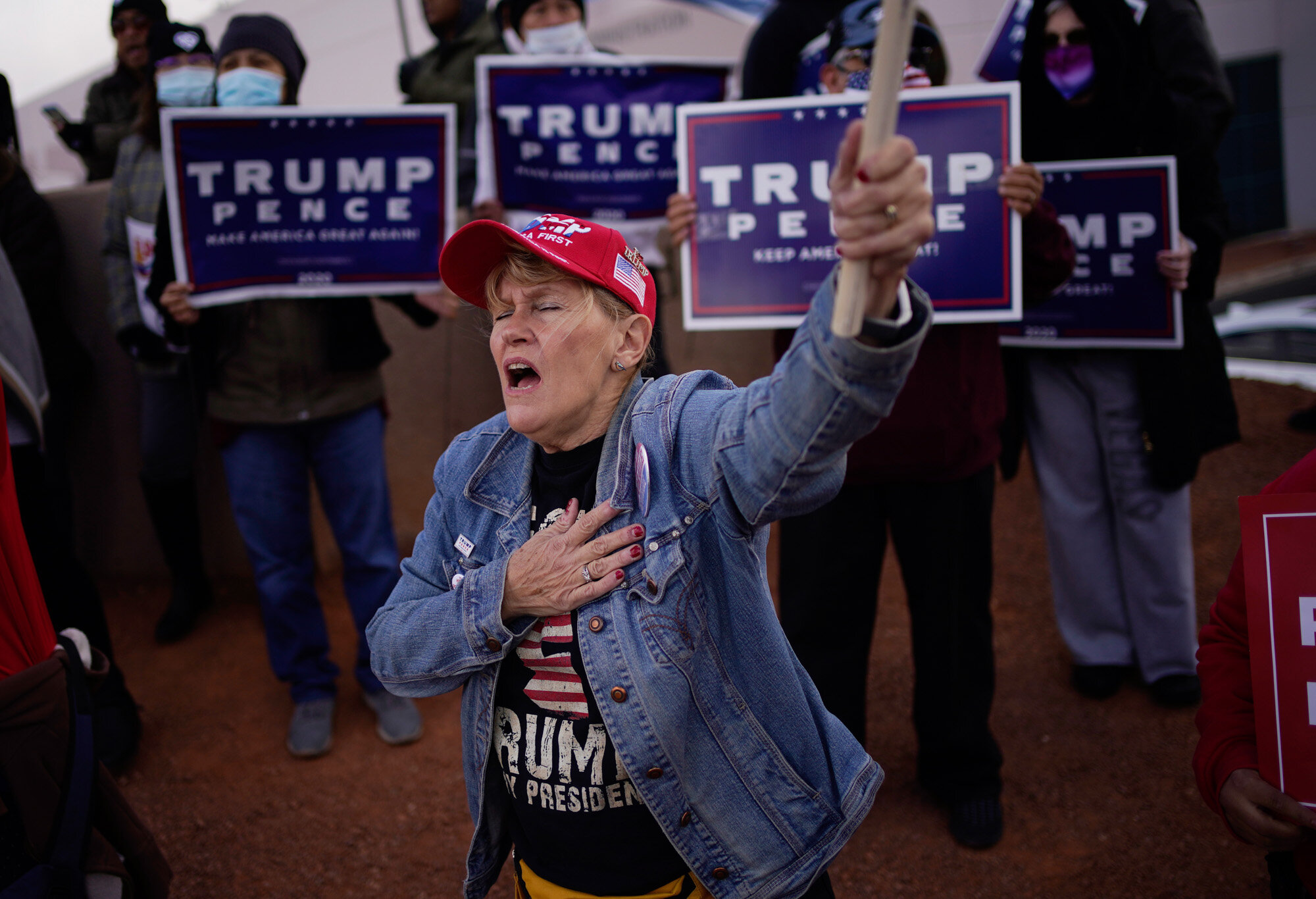A supporter of President Donald Trump holds her hand over her heart during a protest of the election outside of the Clark County Election Department in North Las Vegas on Nov. 8, 2020. (AP Photo/John Locher)