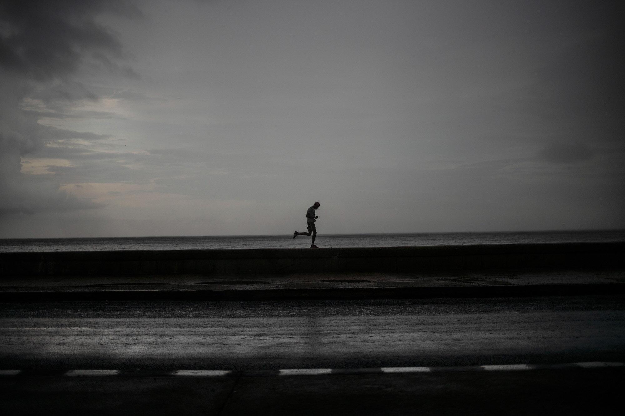 A man wearing a face mask as a precaution against the spread of the coronavirus runs along the Malecon seawall under the rain in Havana, Cuba, on Oct. 6, 2020. (AP Photo/Ramon Espinosa)