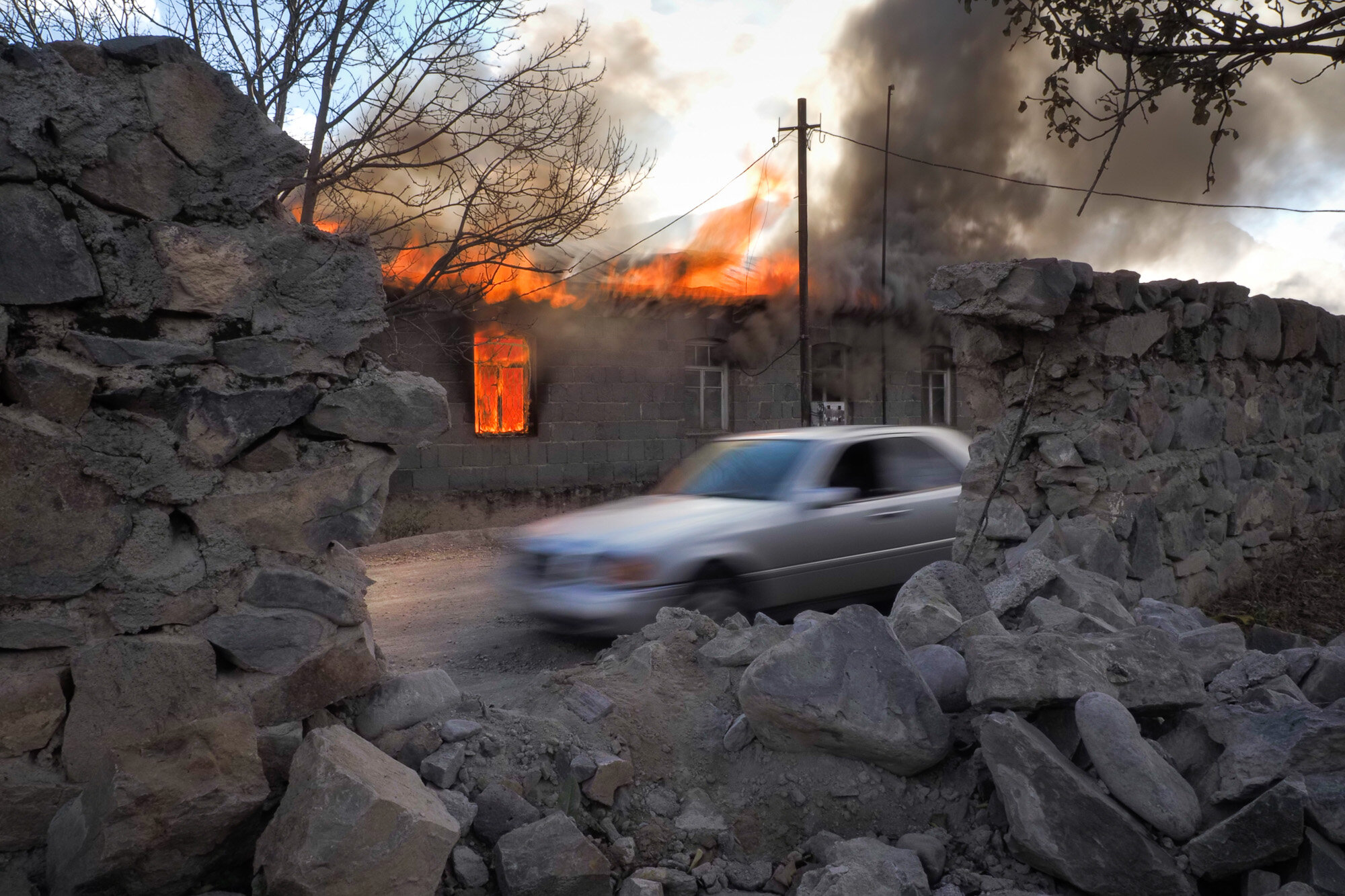 Smoke and flame rise from a burning house in an area once occupied by Armenian forces but soon to be turned over to Azerbaijan, in Karvachar, the separatist region of Nagorno-Karabakh, on Nov. 13, 2020. (AP Photo/Dmitry Lovetsky)