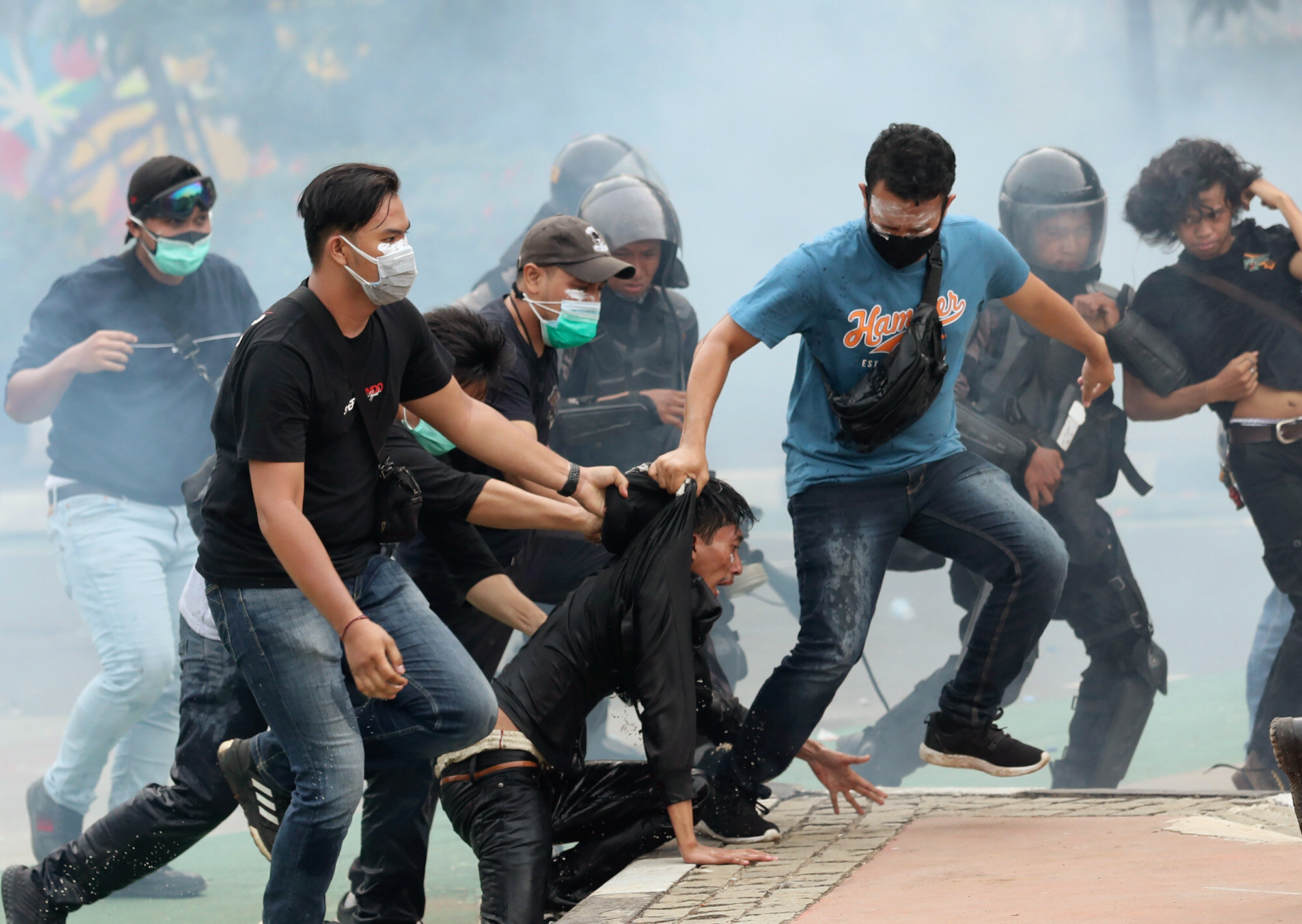 Plainclothes police officers detain demonstrators in Jakarta, Indonesia, on Oct. 8, 2020, during a protest against a new law they say will cripple labor rights and harm the environment. (AP Photo/Tatan Syuflana)
