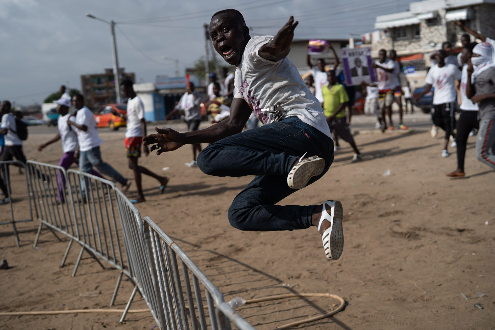 A supporter of presidential candidate Kouadio Konan Bertin jumps a fence as he arrives at Bertin's final campaign rally in Abidjan, Ivory Coast, on Oct. 29, 2020, ahead of the Oct. 31 election. (AP Photo/Leo Correa)