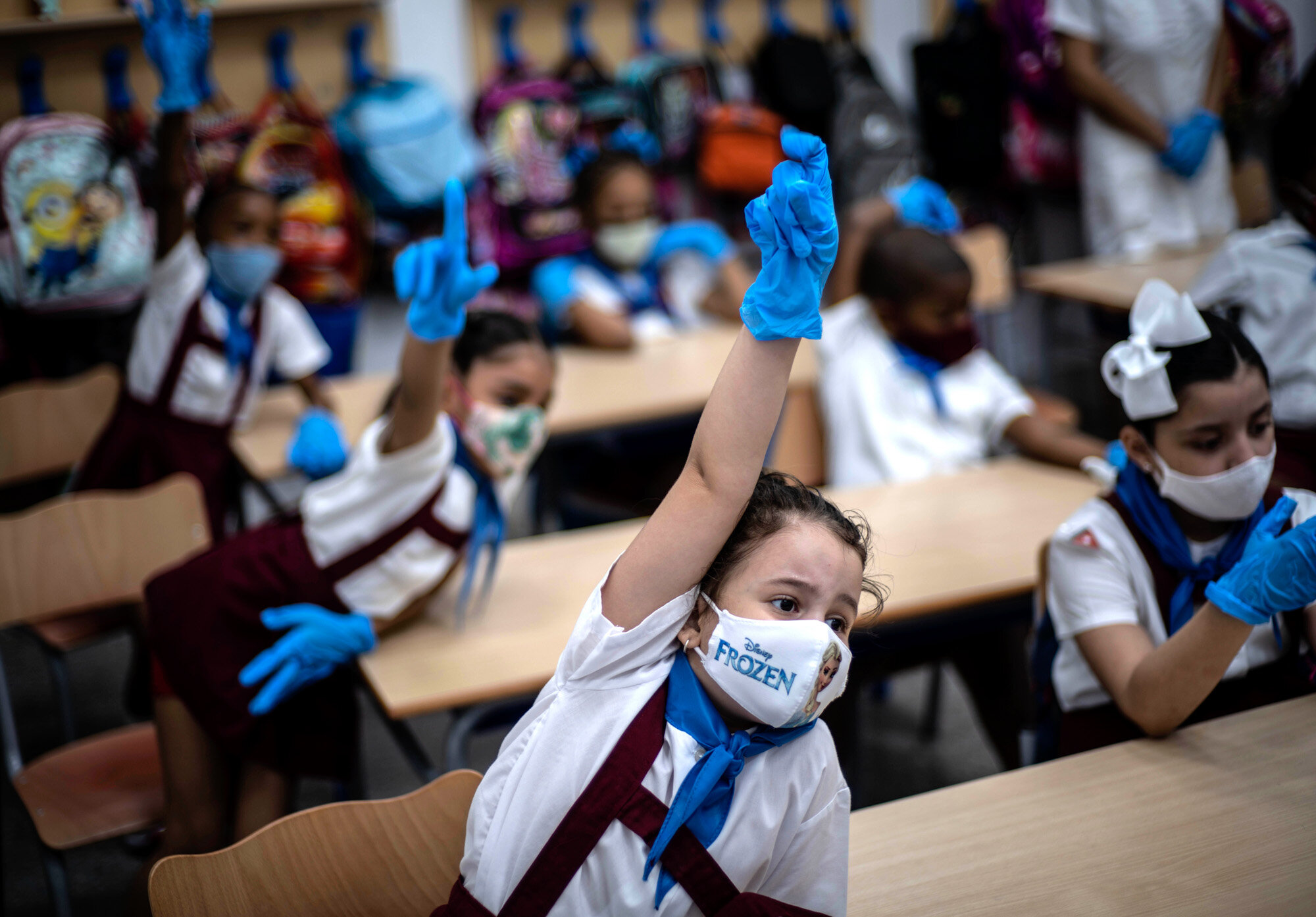 Wearing masks and plastic gloves to prevent the spread of the coronavirus, girls raise their hands during class in Havana, Cuba, on Monday, Nov. 2, 2020. Tens of thousands of school children returned to class Monday in Havana for the first time since April. (AP Photo/Ramon Espinosa)