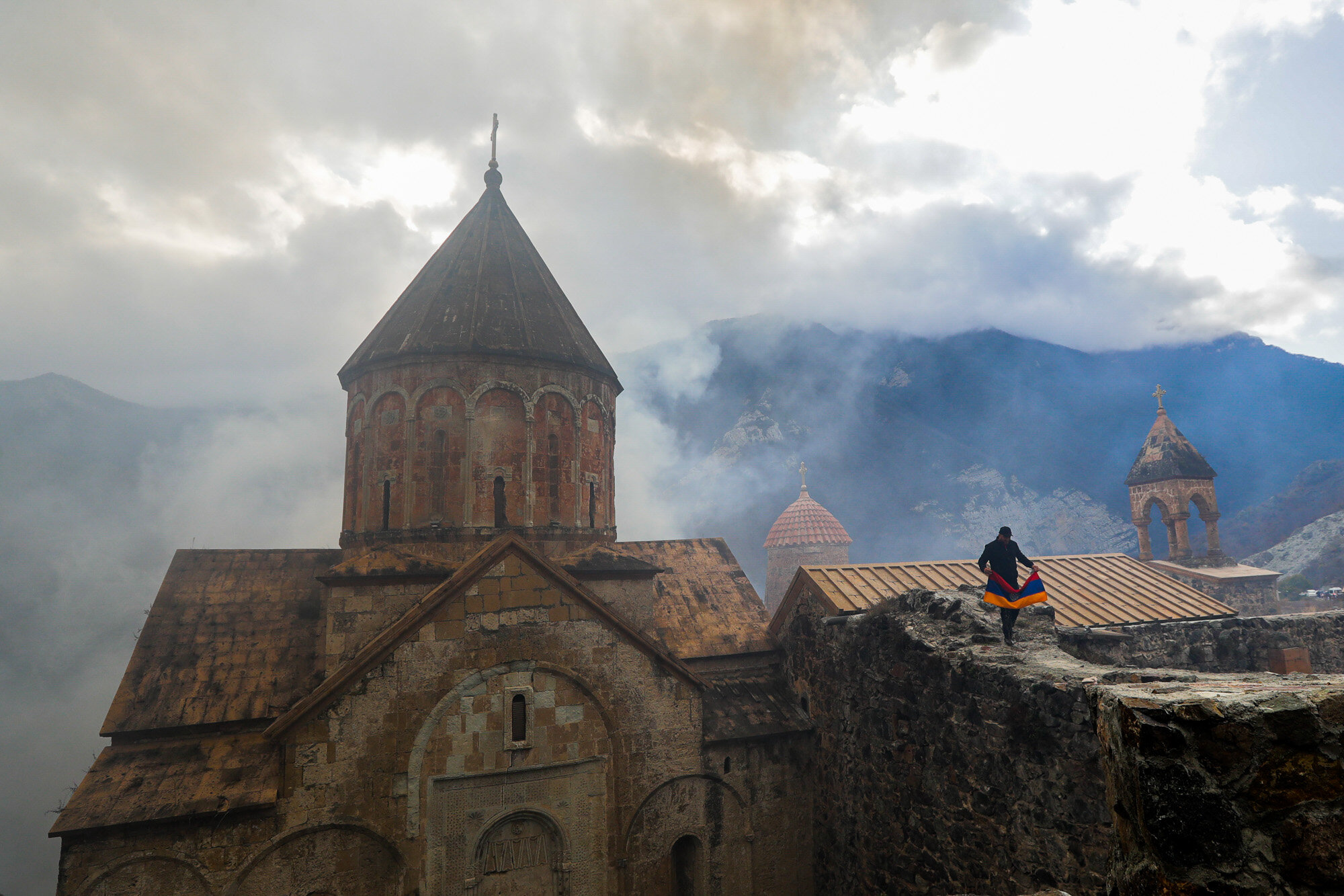 A man with an Armenian national flag visits the 12th-13th century Orthodox Dadivank Monastery on the outskirts of Kalbajar, in the separatist region of Nagorno-Karabakh, on Nov. 13, 2020. Under an agreement ending weeks of intense fighting over the Nagorno-Karabakh region, some Armenian-held territories, such as this area, will pass to Azerbaijan. (AP Photo/Sergei Grits)