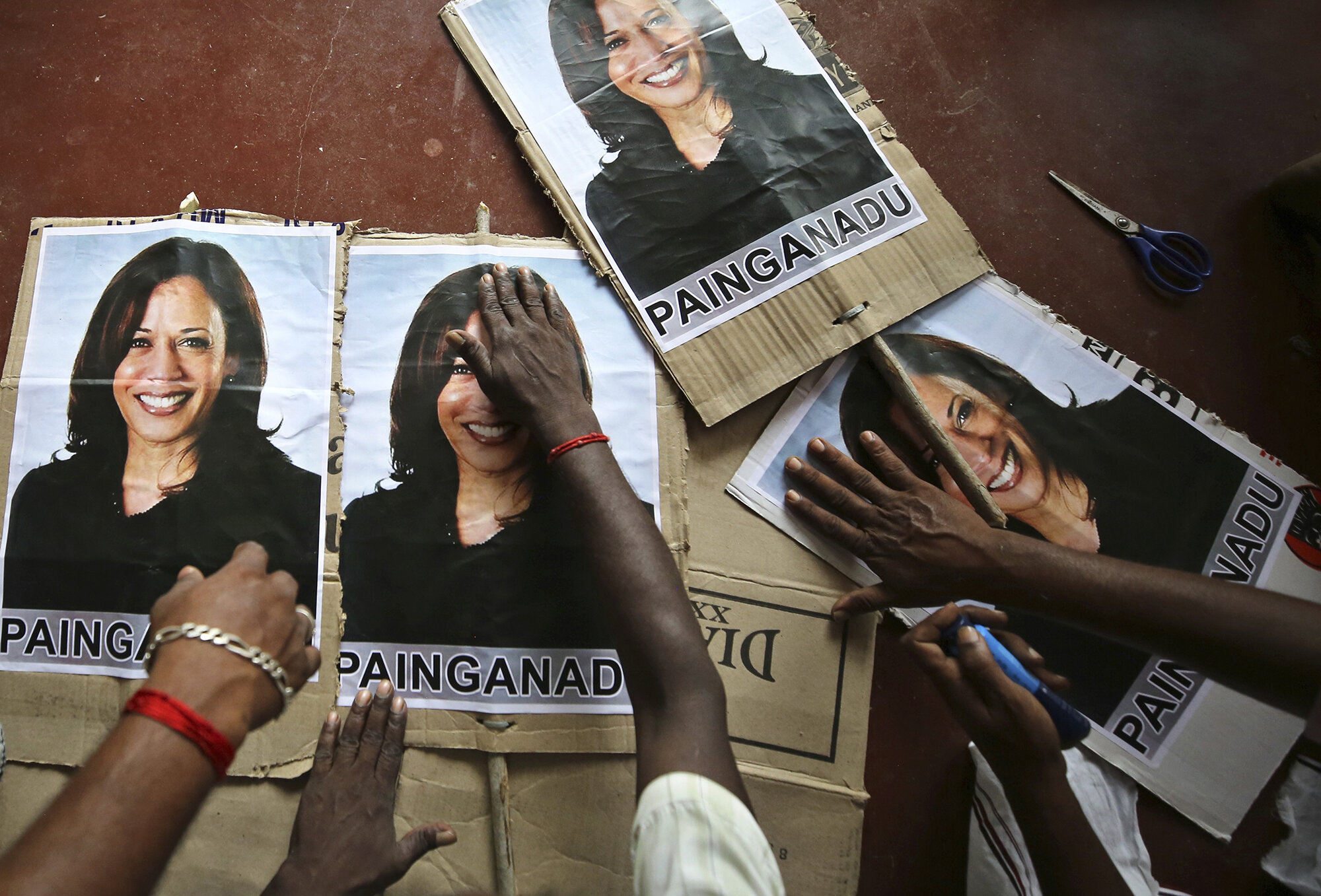 Villagers prepare placards featuring U.S. Democratic vice presidential candidate Sen. Kamala Harris in Painganadu, a neighboring village of Thulasendrapuram, south of Chennai, in Tamil Nadu state, India, Nov. 6, 2020. The lush green village of Thulasendrapuram is the hometown of Harris' maternal grandfather, who migrated from here decades ago. (AP Photo/Aijaz Rahi)