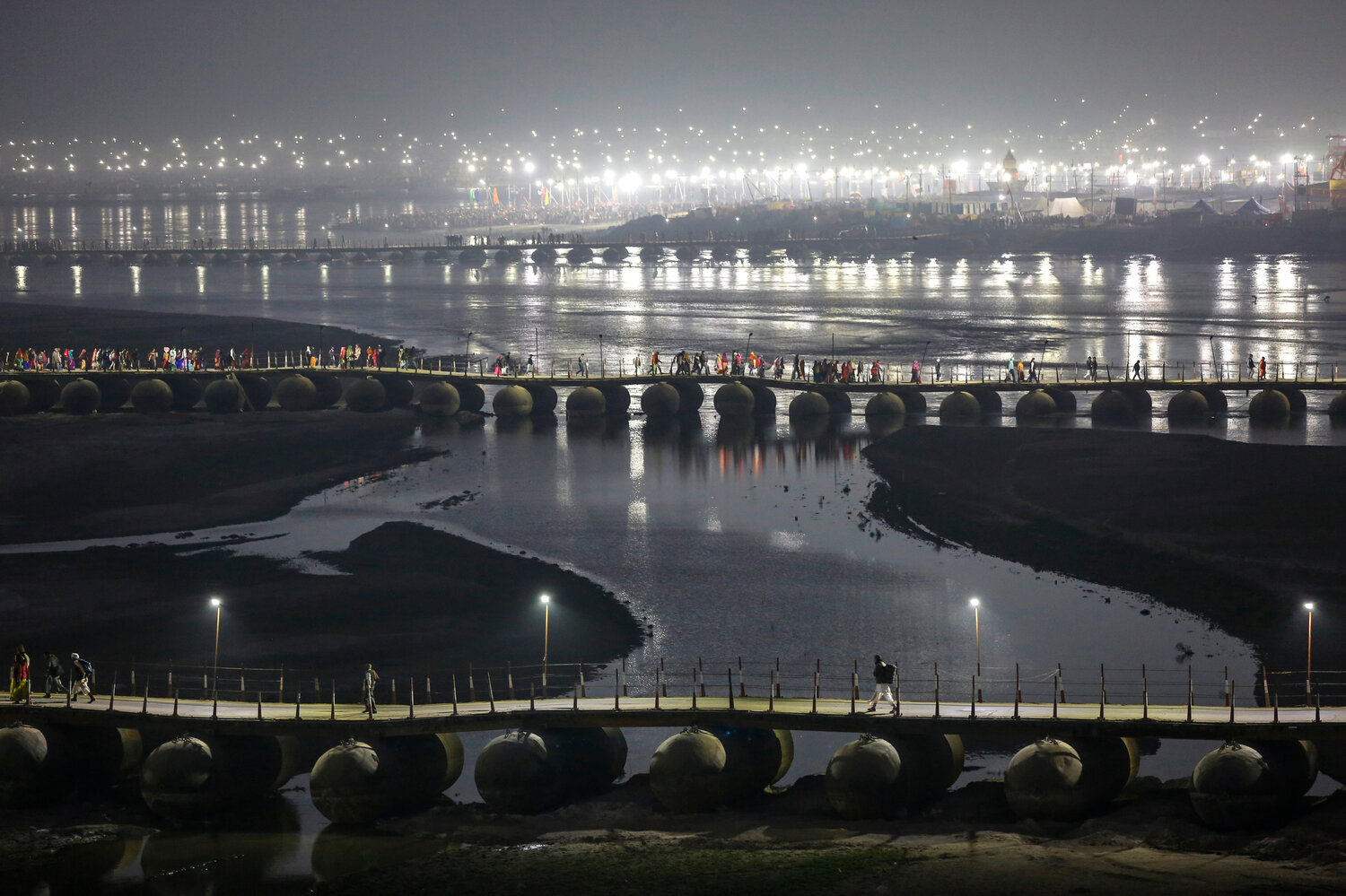 Indian Hindu pilgrims walk through a pontoon bridge before dawn at Sangam, the confluence of rivers Ganges, Yamuna, and mythical Saraswati during Magh Mela, a festival that attracts millions of pilgrims every year, in Prayagraj, in the northern Indian state of Uttar Pradesh on Jan. 30, 2020. (AP Photo/Altaf Qadri)
