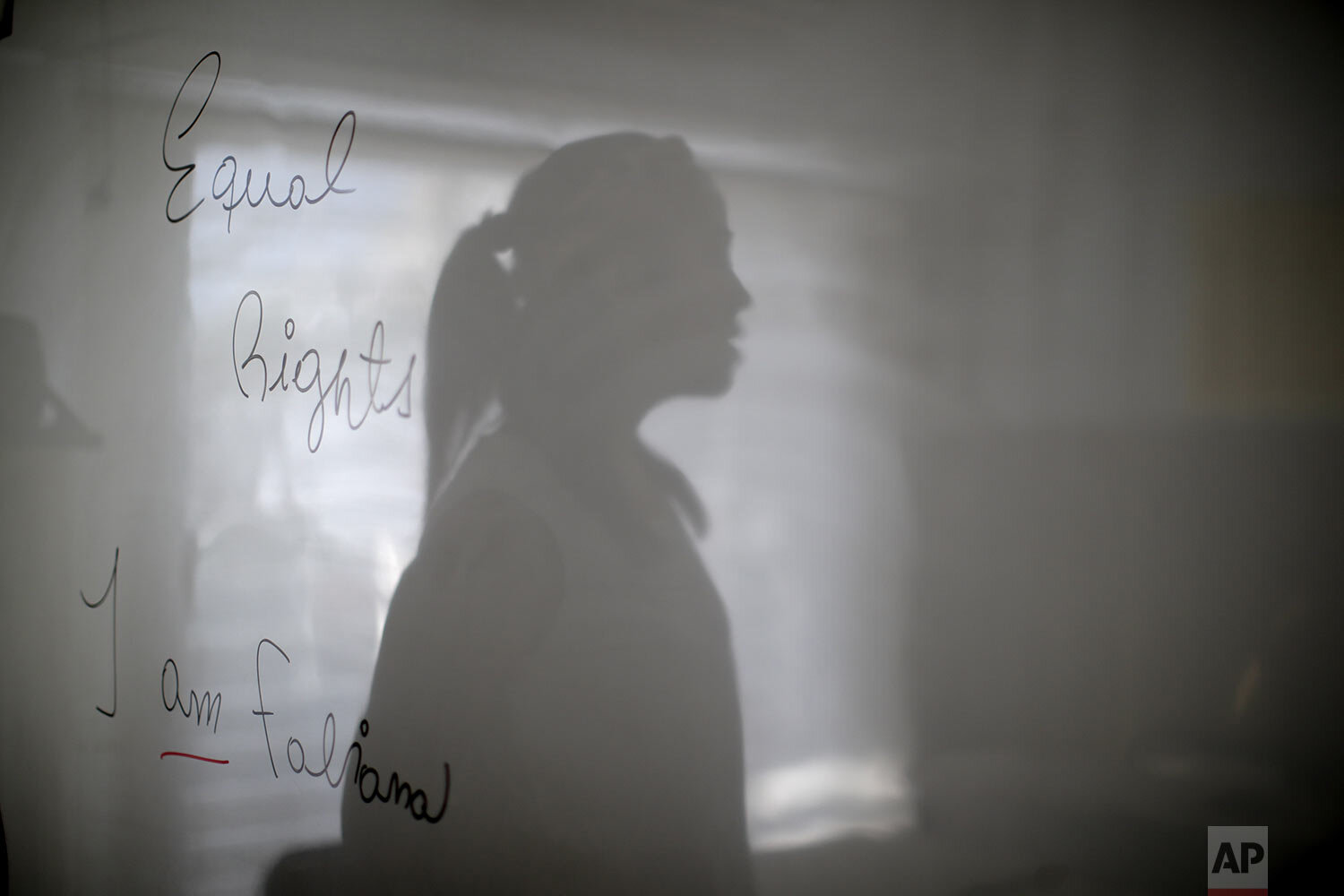 """Transgender woman Fabiana Rodríguez, an English teacher, poses for a portrait with her shadow overlaying the message she wrote on her blackboard: """"Equal rights, I am Fabiana"""" during an interview at the English Institute where she works as a language teacher in Buenos Aires, Argentina, Friday, Nov. 13, 2020. In September, President Alberto Fernández signed a decree establishing a 1% employment quota for transgender people in the public sector. (AP Photo/Natacha Pisarenko)"""
