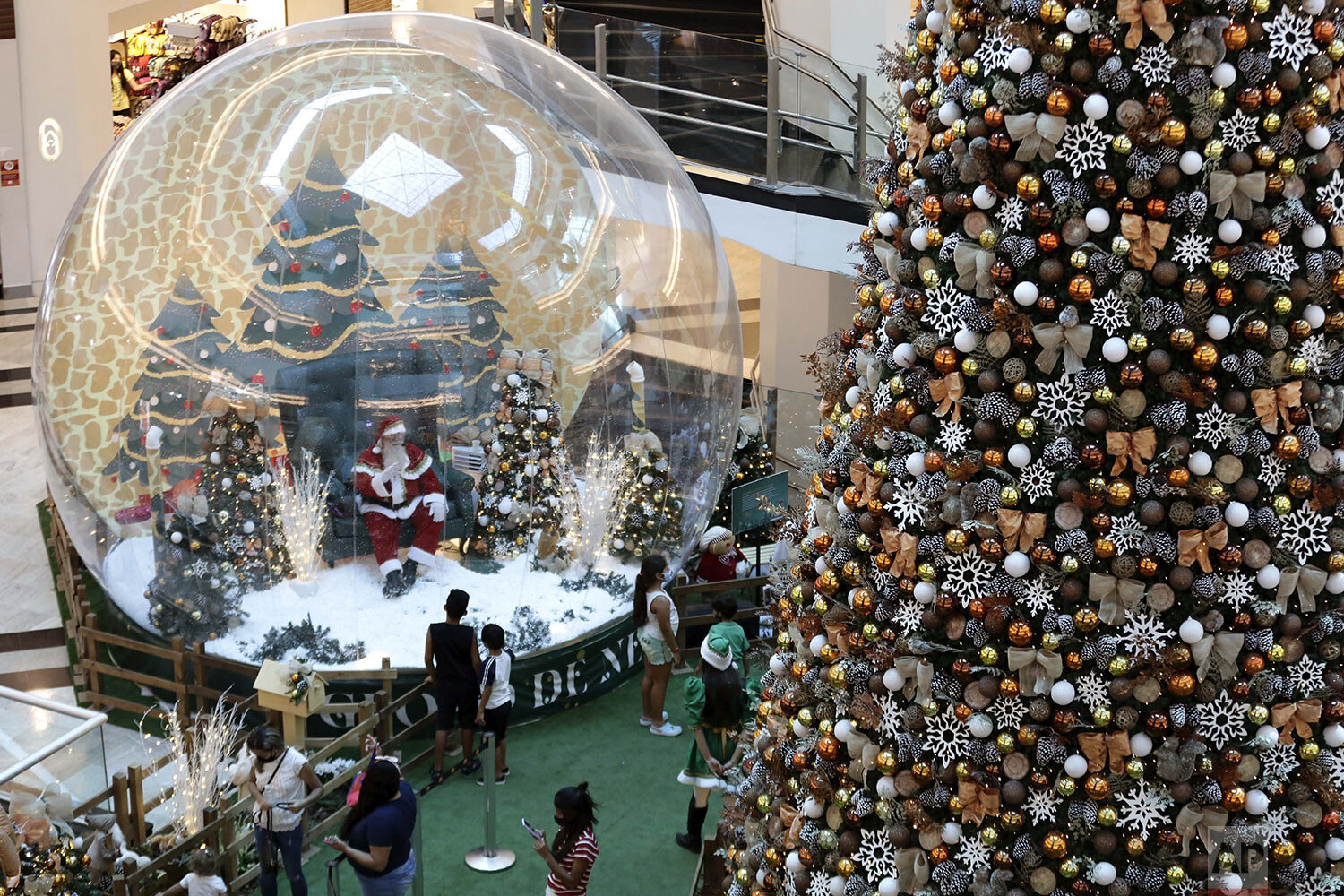 Santa Claus performer Abilio Nunes greets a child from inside a life-size snow globe, as a protective measure amid the spread of COVID-19, at a shopping center in Brasilia, Brazil, Wednesday, Dec. 16, 2020. (AP Photo/Eraldo Peres)