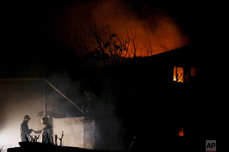 Firefighters work the scene of a fire at La Chacarita neighborhood on Christmas Eve, in Asunción, Paraguay, Friday, Dec. 25, 2020. (AP Photo/Cesar Olmedo)
