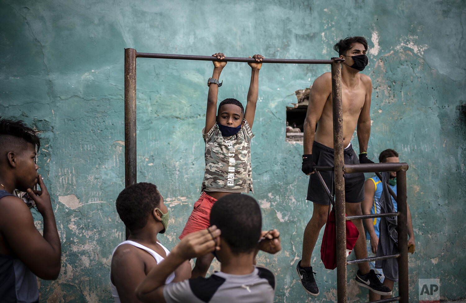 Youths exercise at a street gym in Havana, Cuba, Monday, Dec. 21, 2020, during the COVID-19 pandemic. (AP Photo/Ramon Espinosa)