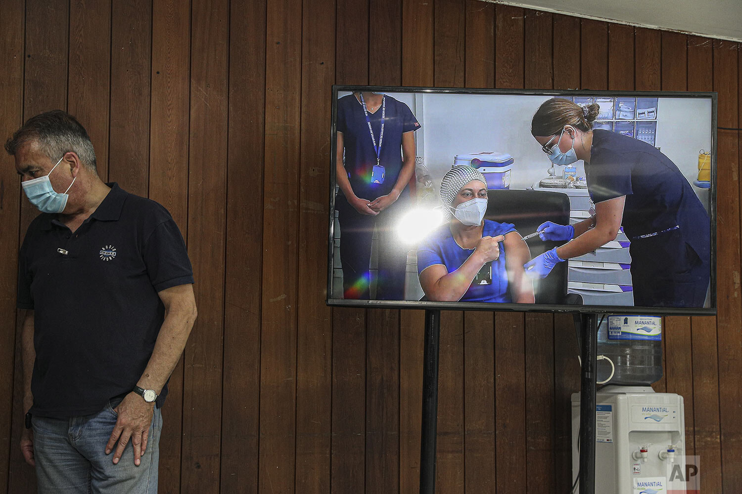 A monitor shows a live video image of nurse Zulema Riquelme getting the first shot of the COVID-19 vaccine at the Metropolitan Hospital in Santiago, Chile, Thursday, Dec. 24, 2020, after the first batches of Pfizer vaccines arrived. (AP Photo/Esteban Felix)