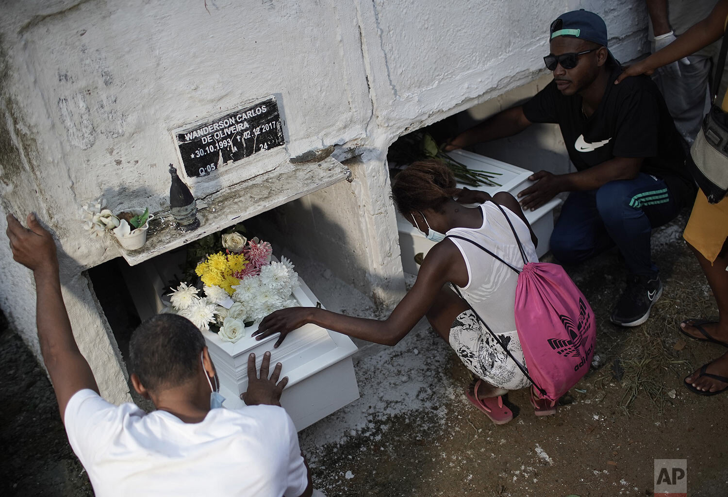 Relatives of cousins Emily Victoria Silva dos Santos, 4, and Rebeca Beatriz Rodrigues dos Santos, 7, kneel by their coffins as they bury the cousins in Duque de Caxias, Rio de Janeiro state, Brazil, Saturday, Dec. 5, 2020. Grieving families held funerals for the girls killed by bullets while playing outside their homes. (AP Photo/Silvia Izquierdo)
