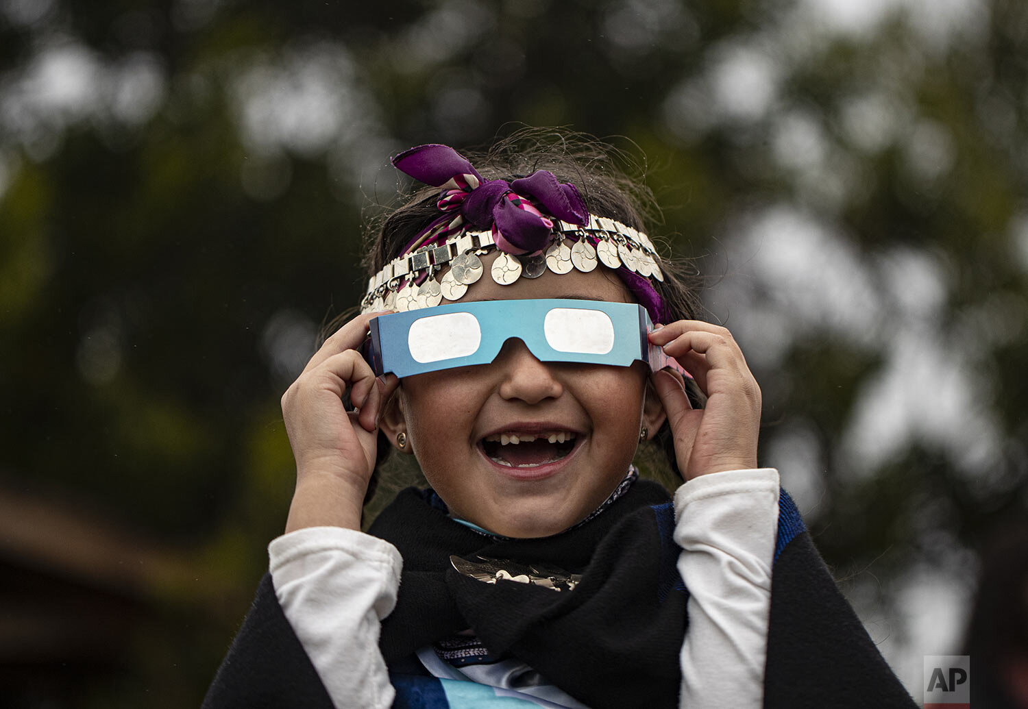 Magdalena Nahuelpan, a Mapuche Indigenous girl, uses special glasses to look at a total solar eclipse in Carahue, La Araucania, Chile, Monday, Dec. 14, 2020. (AP Photo/Esteban Felix)