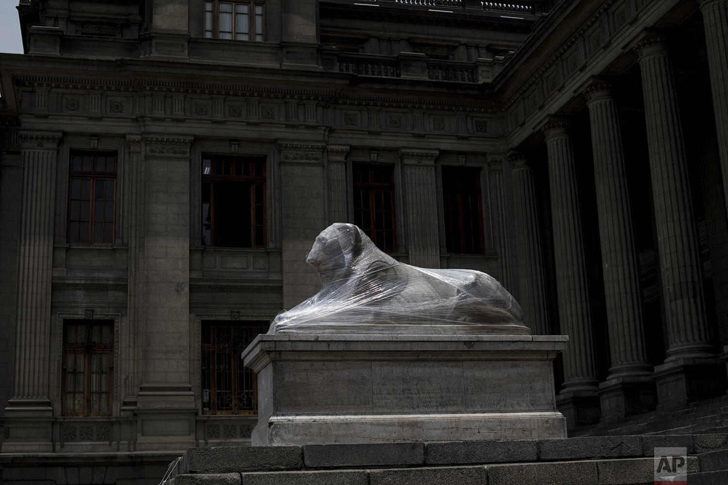 A lion statue outside the Palace of Justice is wrapped in plastic during maintenance in Lima, Peru, Tuesday, Dec. 1, 2020. Monuments were practically spared by protesters decrying a parliamentary coup in early November when Congress voted to oust ex-President Martín Vizcarra. (AP Photo/Rodrigo Abd)
