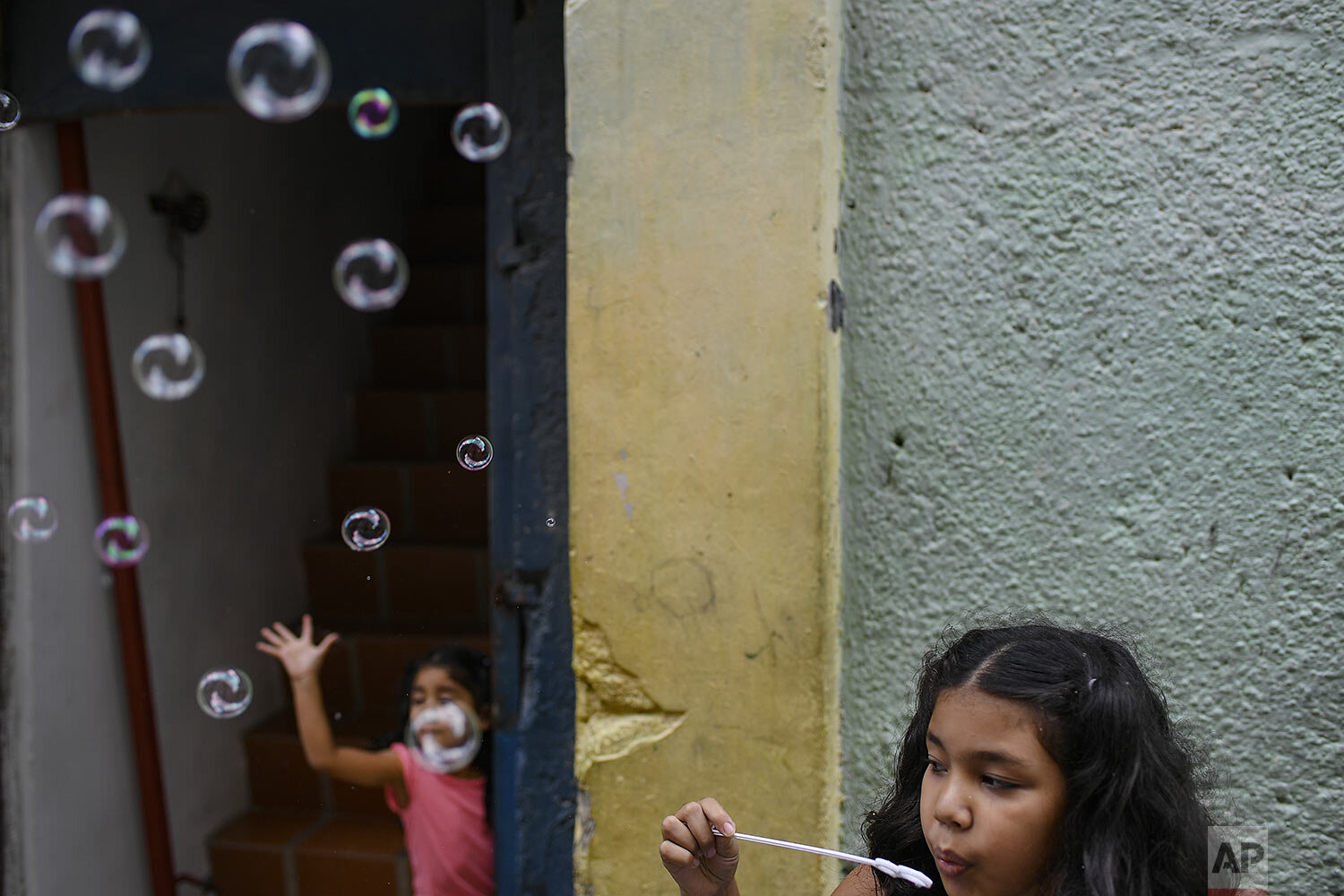 Sisters play with soap bubbles in the Catia neighborhood on Christmas Day in Caracas, Venezuela, Friday, Dec. 25, 2020, amid the new coronavirus pandemic. (AP Photo/Matias Delacroix)