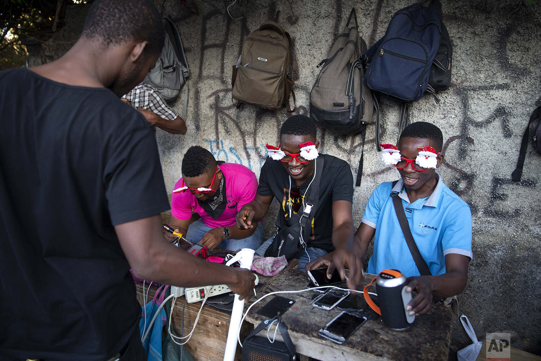 Cellphone repairmen wear Santa Clause themed glasses as they ply their trade on the sidewalk in Port-au-Prince, Haiti, Thursday, Dec. 24, 2020. (AP Photo/ Dieu Nalio Chery)
