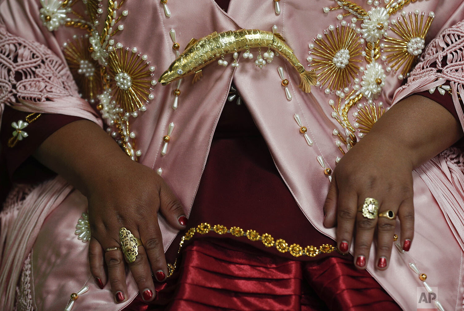 A woman shows off her jewelry before performing at a Chola fashion show in La Paz, Bolivia, Friday, Dec. 4, 2020, an event that designers and manufacturers of Chola clothing hope reactivates their economy. (AP Photo/Juan Karita)
