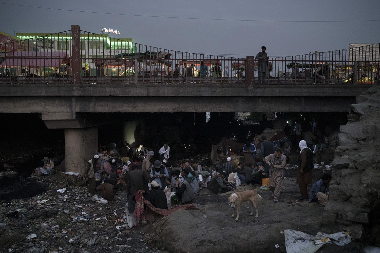 Afghánci se shromažďují pod mostem, aby ve čtvrtek 30. září 2021 konzumovali drogy, převážně heroin a metamfetaminy, v afghánském Kábulu. (AP Photo/Felipe Dana)