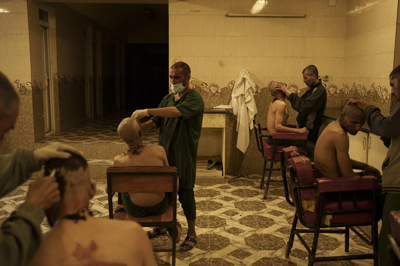 Uživatelé drog zadržení během náletu Talibanu se oholí po příjezdu do avicenské lékařské nemocnice pro protidrogovou léčbu v Kábulu v Afghánistánu, pátek, 1. října 2021. (AP Photo/Felipe Dana)