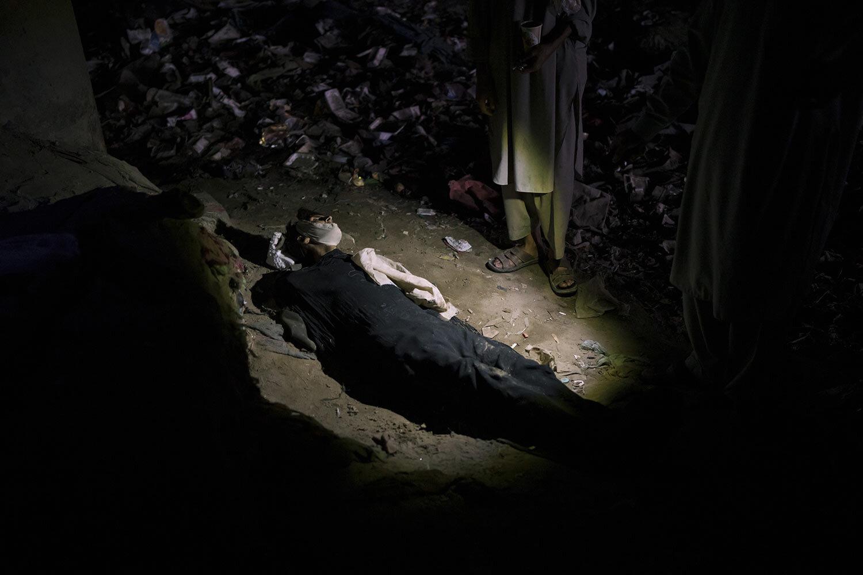 Tělo mrtvého muže leží na zemi v oblasti obývané uživateli drog pod mostem v Kábulu v Afghánistánu, čtvrtek 30. září 2021. (AP Photo/Felipe Dana)