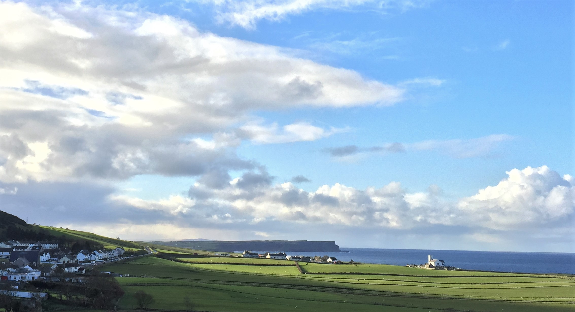 ^Approaching Ballintoy from Carrick-A-Rede. Ballintoy Church to the right, Giant's Causeway cliffs in the distance.