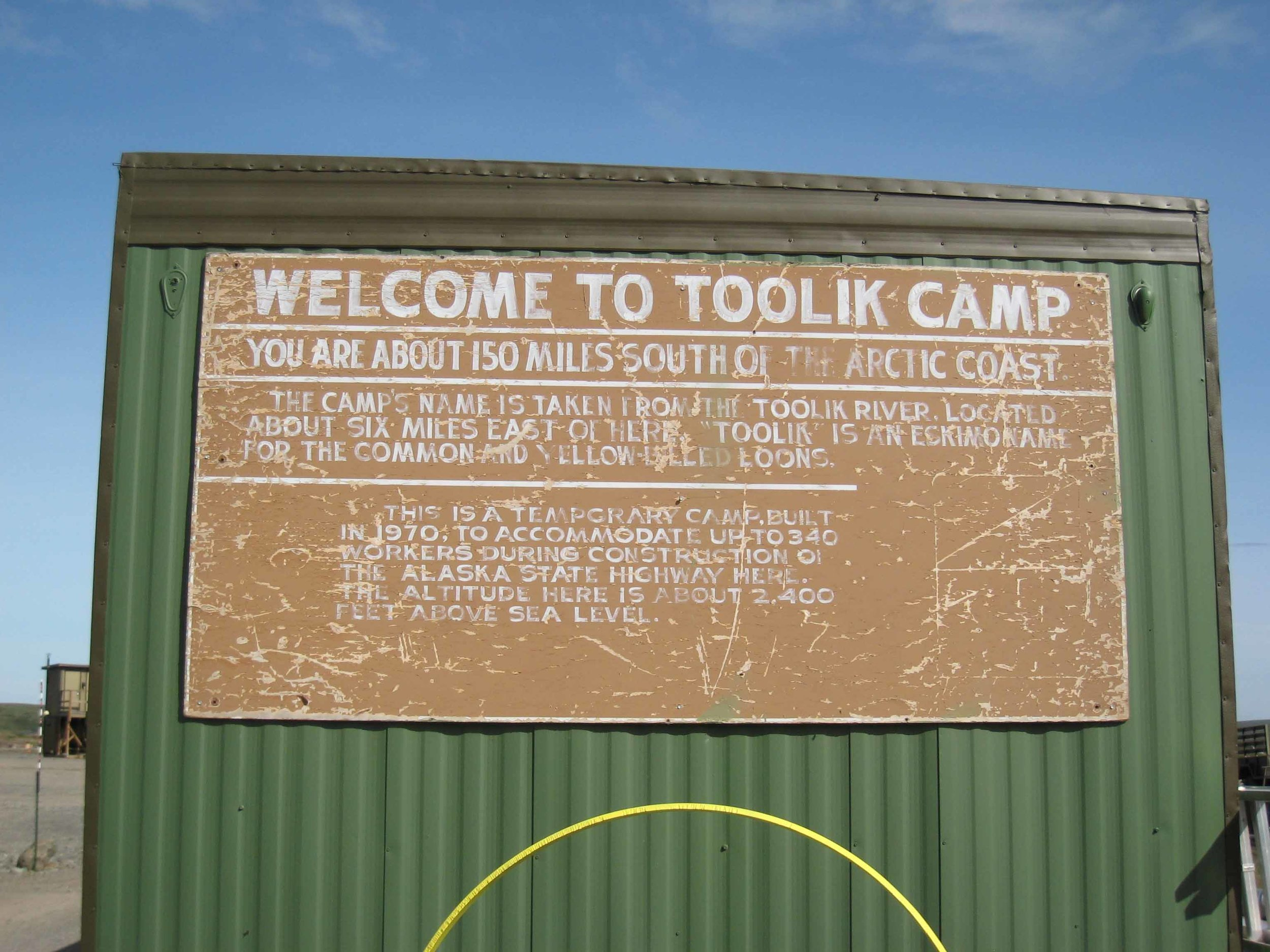 A weathered sign informs visitors about Toolik.