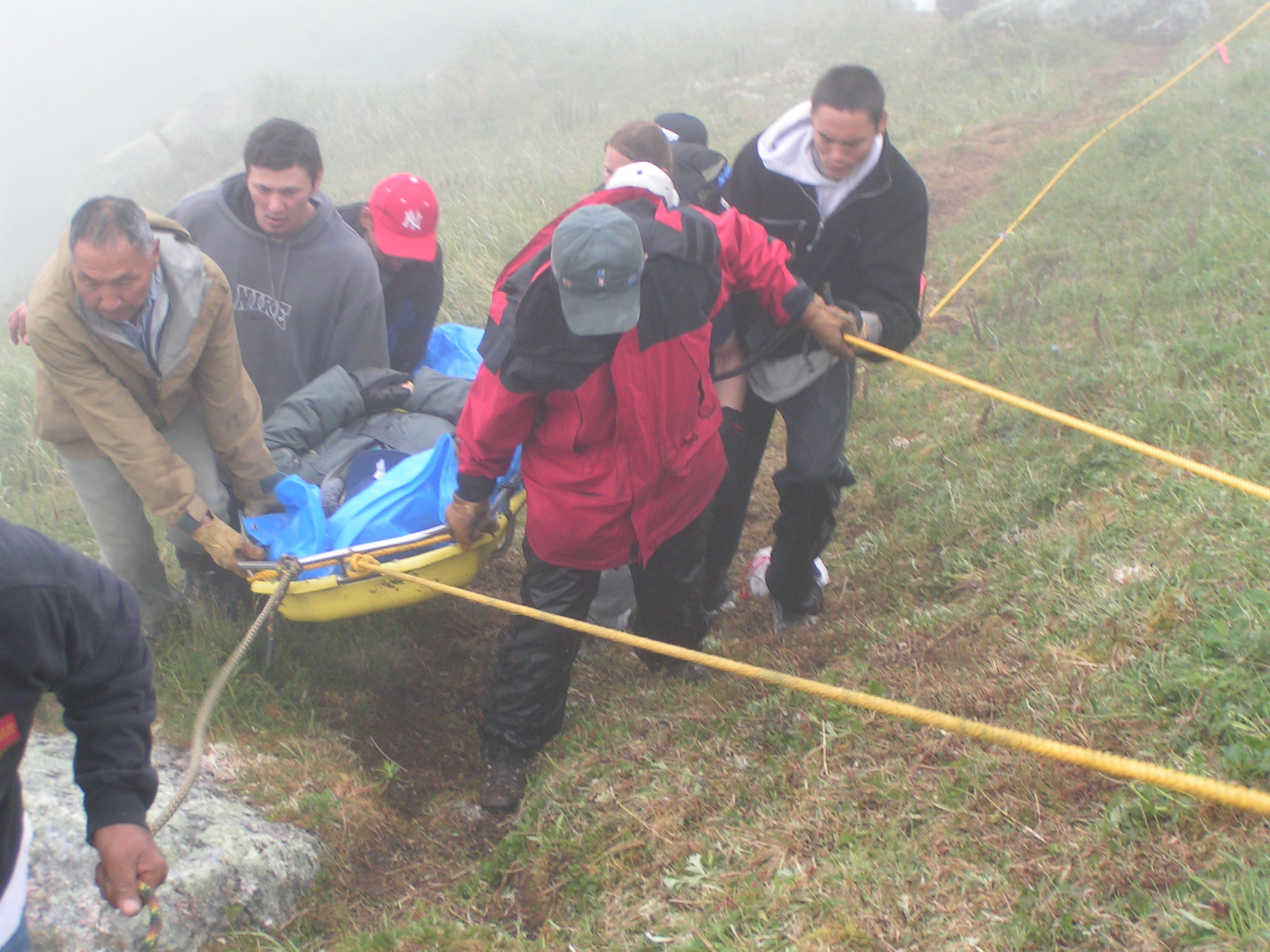 Chico helps a team as it carries the oldest Elder of the King Islanders the top of the island so he could be helicopter-evacuated after his health deteriorated.  A storm delayed the rescue for two days. King Island, 2004.