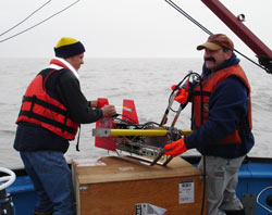 Steve Okkenen from the University of Alaska, Fairbanks, and Phil Alatalo from Woods Hole Oceanographic Institution deploy the Acrobat, an instrument towed by the boat to measure water temperature, salinity, and fluorescence. Source: Woods Hole Oceanographic Institute.
