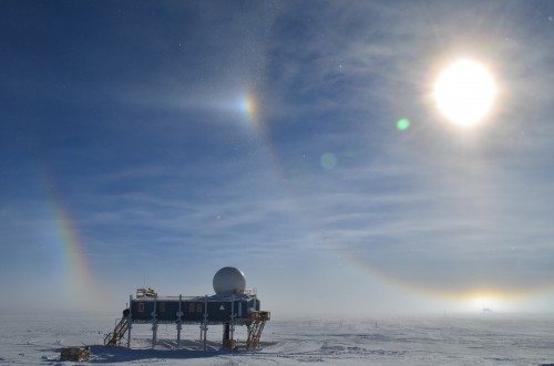 Big House, Summit Station, Greenland, with sundog and double-halo. The Temporary Atmospheric Watch Observatory glows in the distance at lower right. Photo: shawntel stapleton
