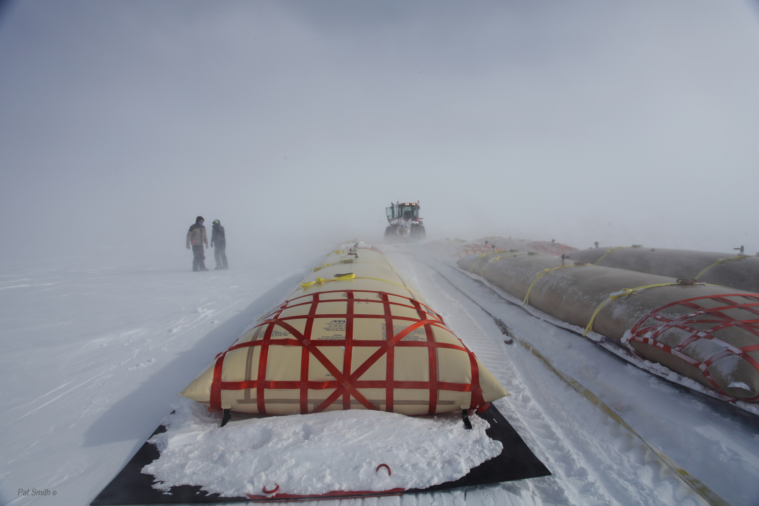 Team members transfer the fuel bladder sled in this May 1, 2011 shot of the Greenland Inland Traverse. Photo: Pat Smith