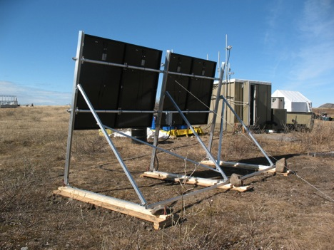 """The back of the new PV array showing additional bracing and tie downs. The array is set at a steep 80 degree angle to maximize power production in the shoulder seasons. The black color and angle should minimize snow accumulation. The bottom of the panels is located 40"""" above grade to prevent being buried in snow drift. All of this produces a significant sail effect, so it is important to hold it down well. We use a combination of pinning with re-bar, ballast and guy cables. Two more side guys are yet to be installed."""