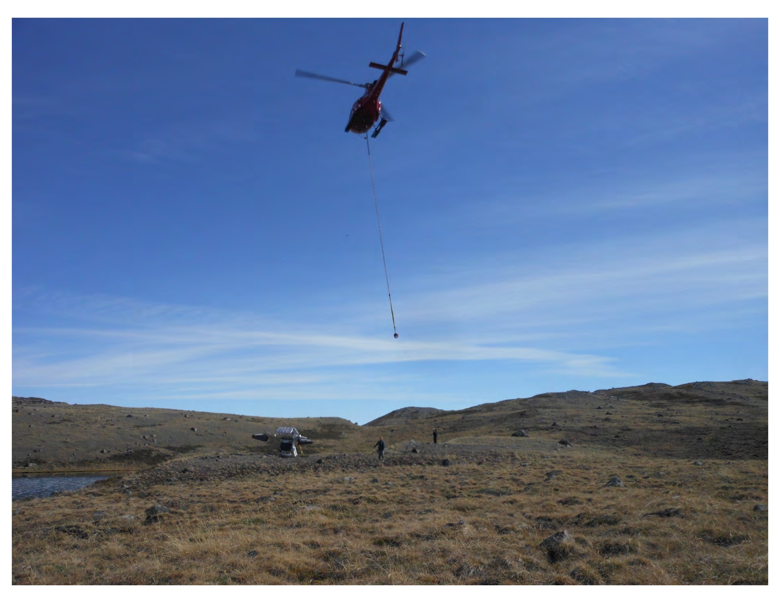 A helicopter lifts the SolarBee so researchers can examine the instrument.