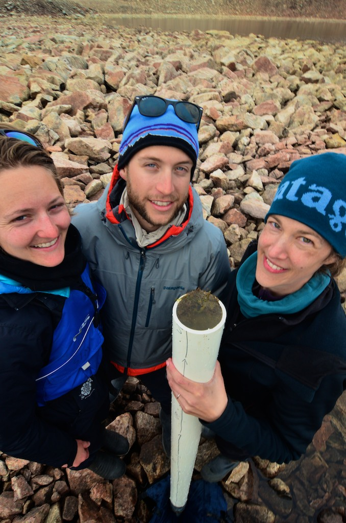 Professor Yarrow Axford (right) Jamie McFarlin (left) and Everett Lasher (center) show off a sediment core recovered from a small non-glacial lake near the Greenland Ice Sheet margin.  Photo: Alex P. Taylor.