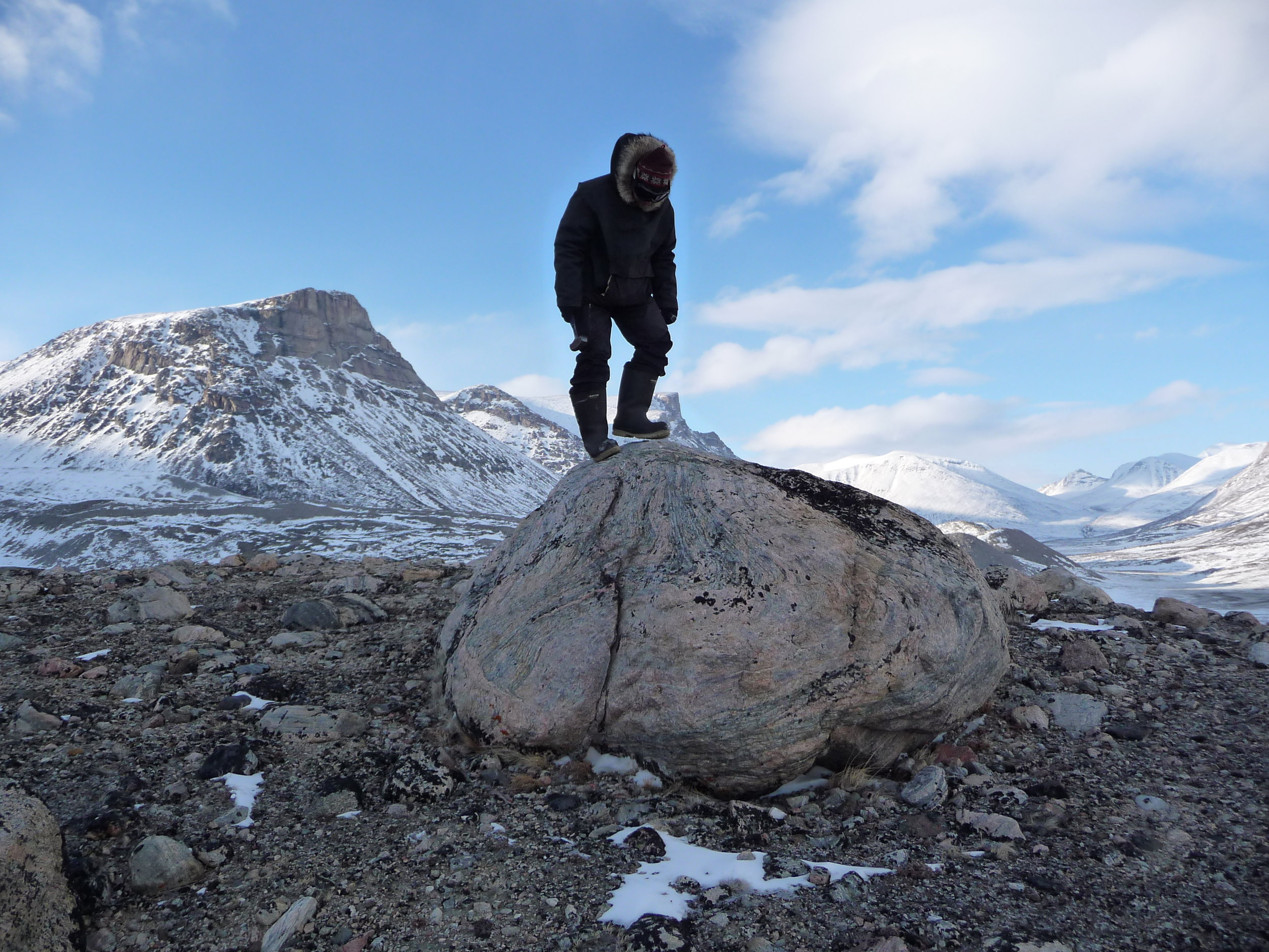 Jason Briner (SUNY Buffalo) sizes up a good looking boulder on Baffin Island before sampling. Photo: Nicolas Young