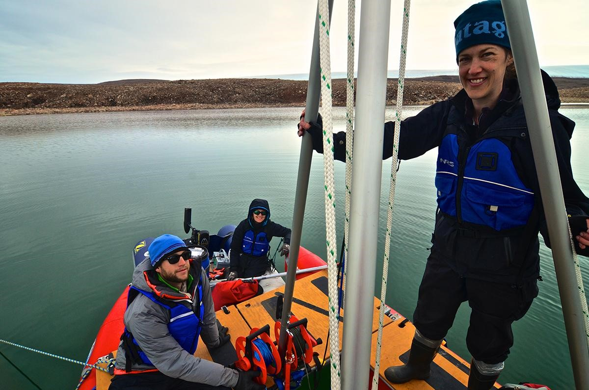 Researcher Yarrow Axford and Ph.D. students prepare to take a sediment core from a lake in northwest Greenland. Photo credit: Alex P. Taylor