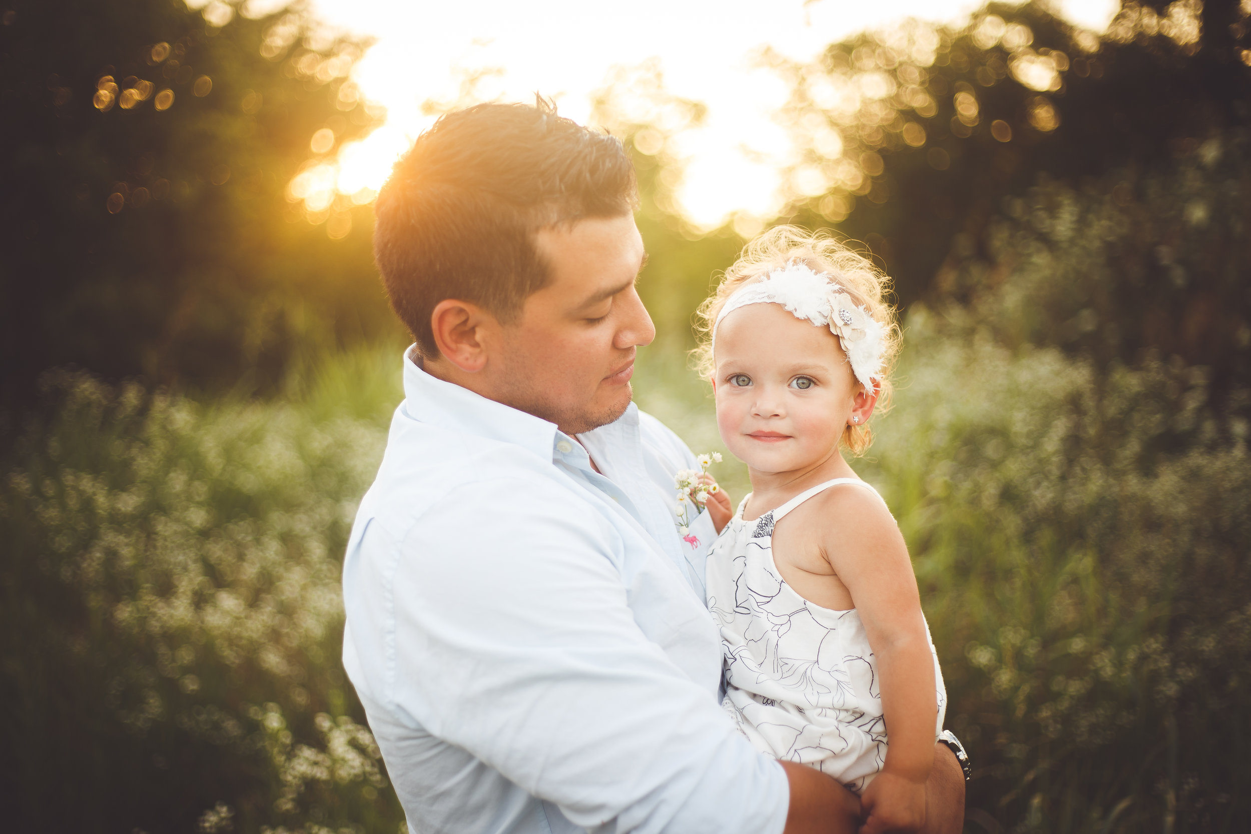 A younf father holds his beautiful young daughter wearing a white headband in his arms