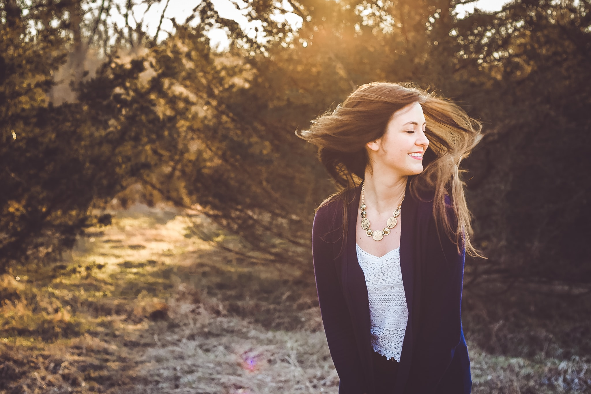 A beautiful, young senior girl turns her head and her long hair turns in the wind in this senior photograph by L+R Photography - Tulsa, OK