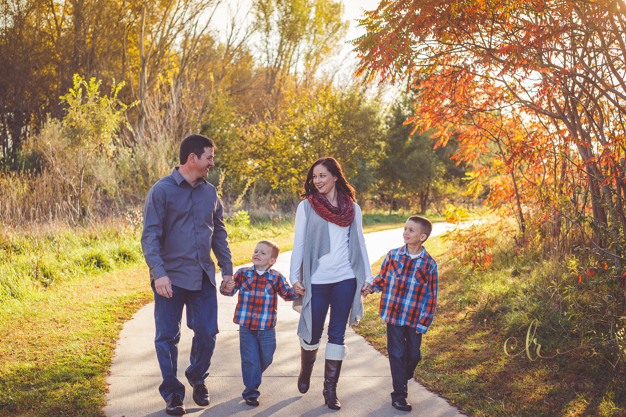 A photograph of a family of four, walking down a park path and holding hands - Tulsa, Oklahoma Family Photographer
