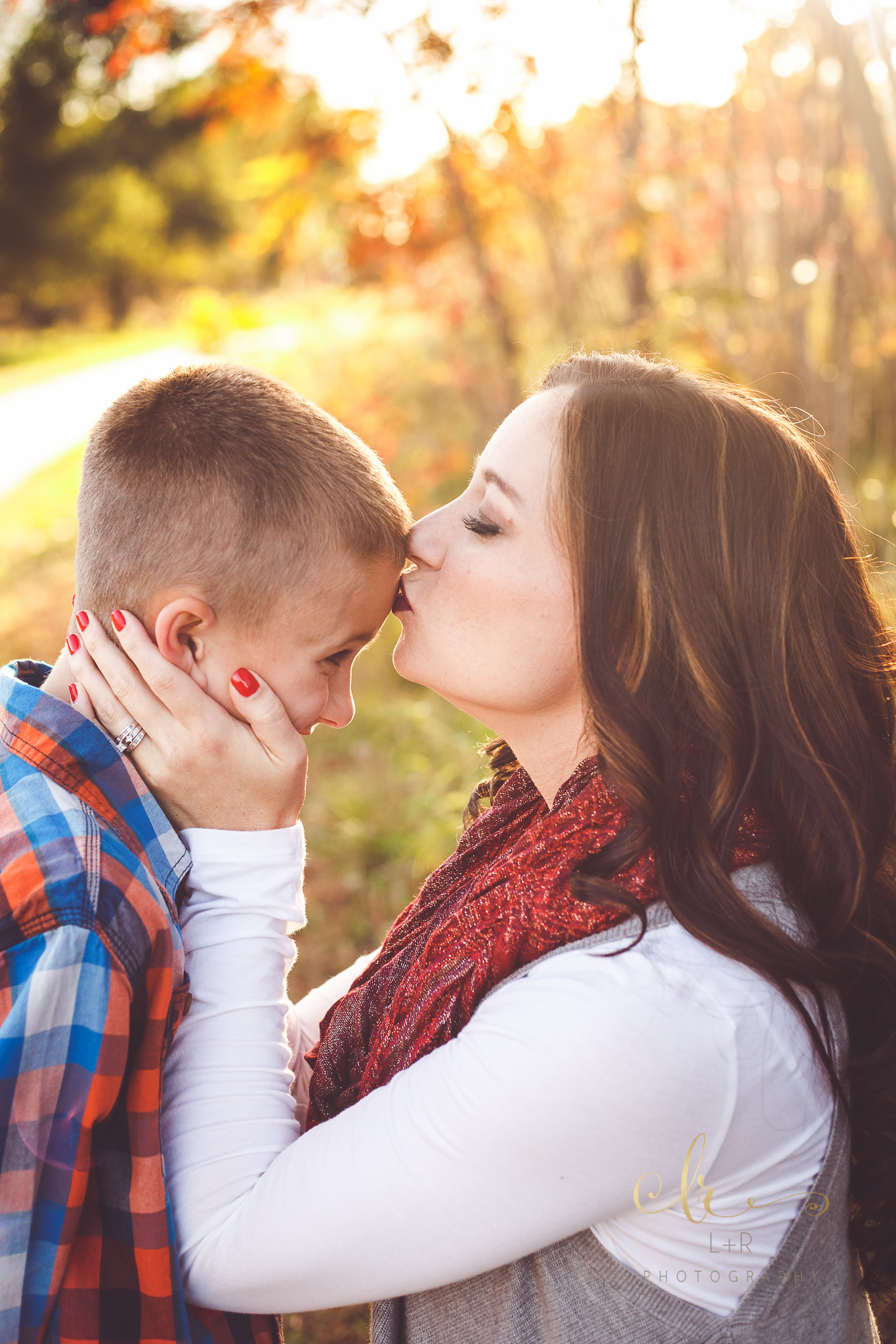 A young mother wearing a striking red scarp tenderly kisses the forehead of her son in this family photograph by L&R Photography of Tulsa, OK