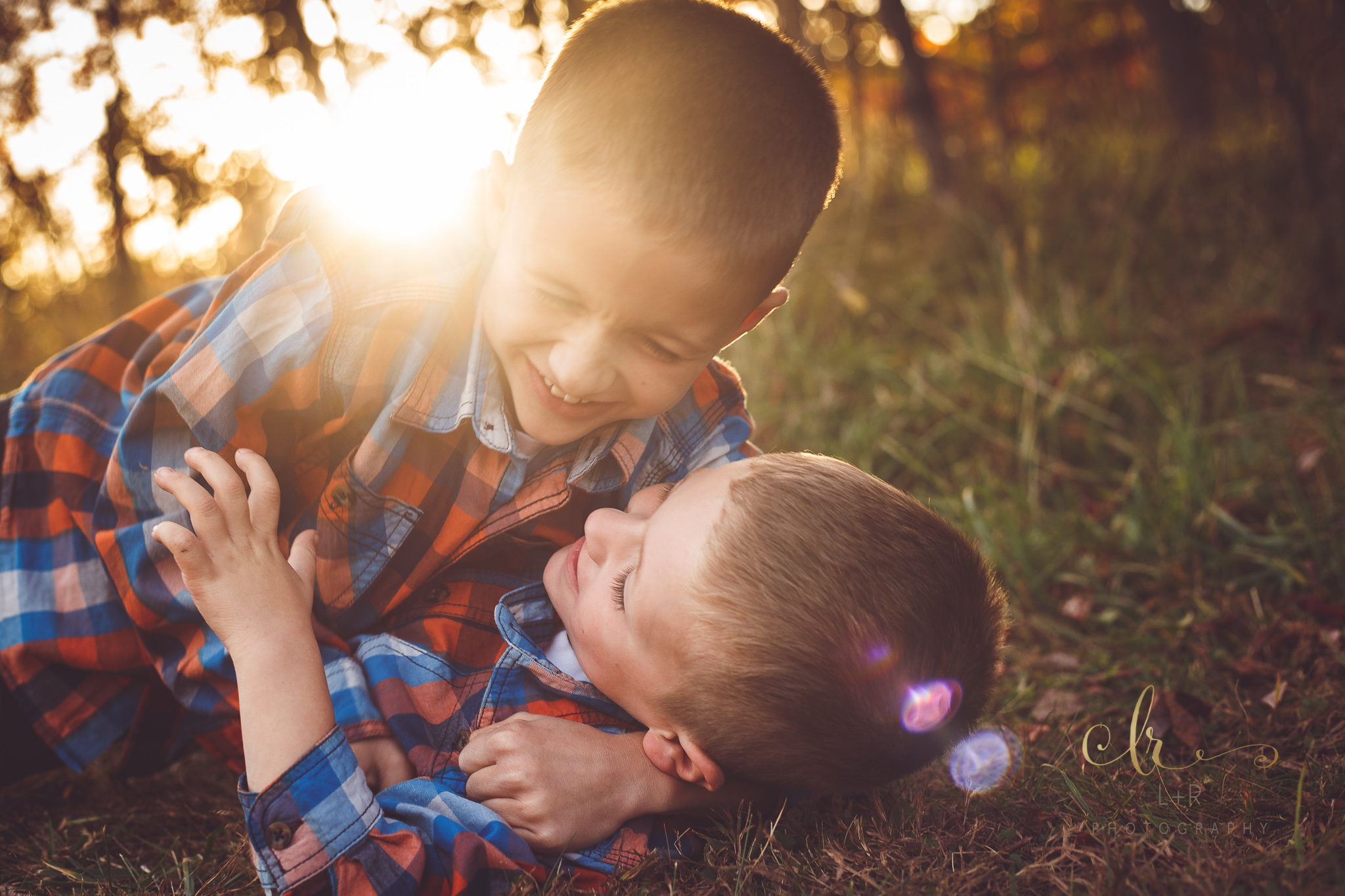 Two young brothers enjoy a moment, wrestling on the ground and laughing during this sunset family photography session by L&R Photography