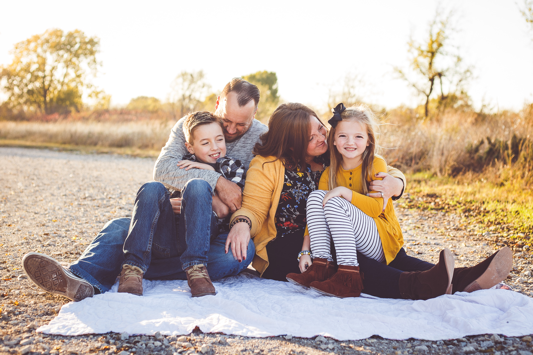 A beautiful family sits together on a blanket at sunset in this family photography session by L+R Photography
