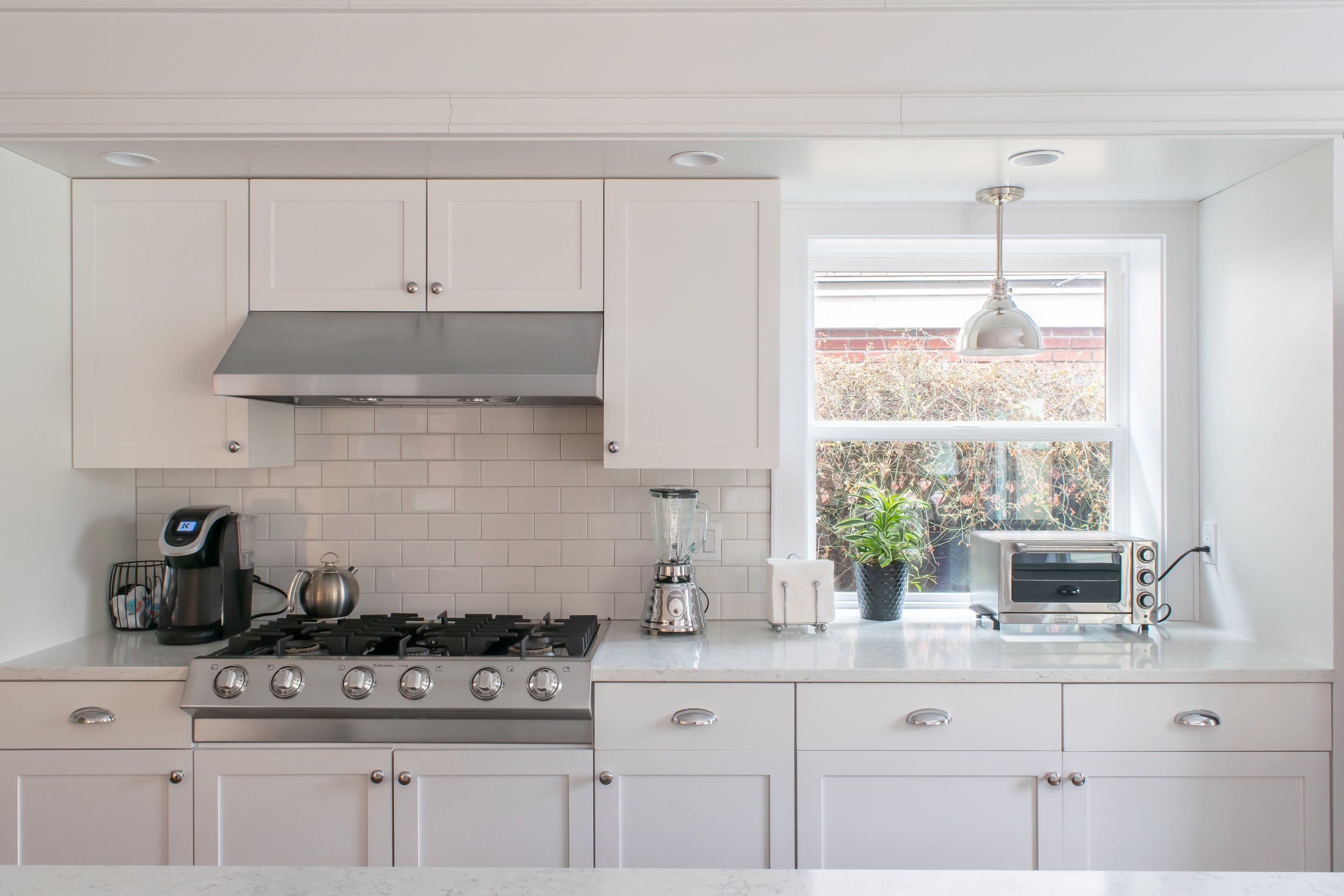 Kitchen counter and cooktop illuminated by natural light