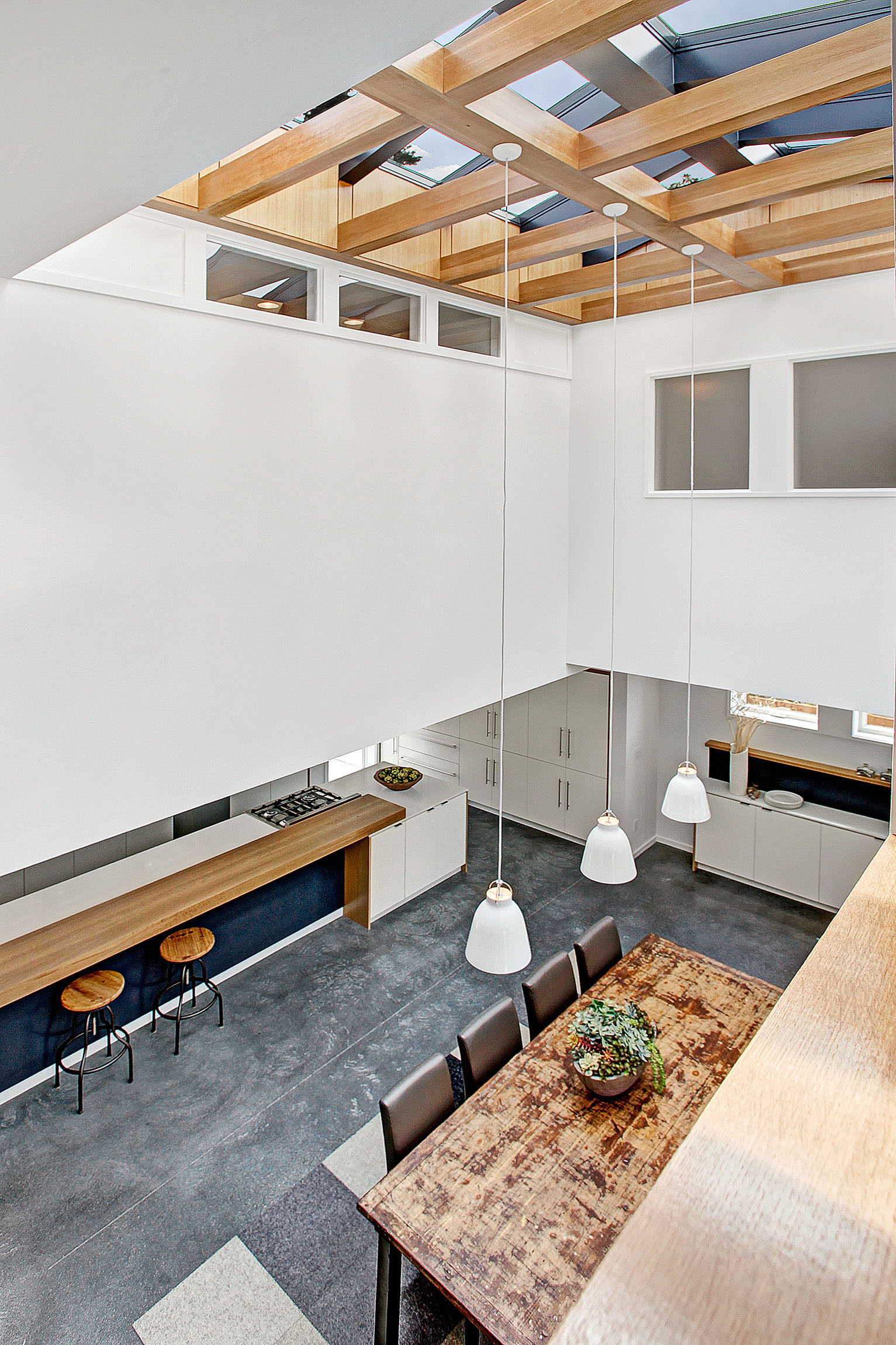 Wood wrapped structure with skylights above makes a special moment above this double height space.