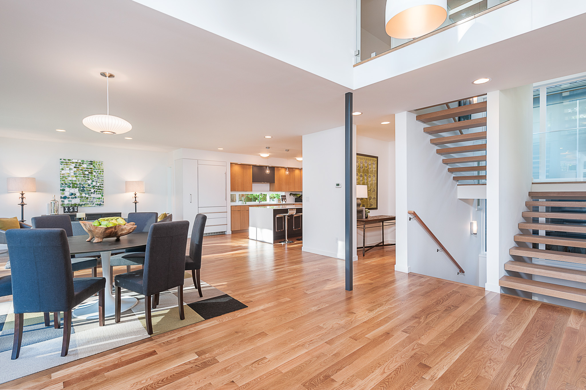 """In the  """"C"""" House , the dogleg stair marches up the center of the house, creating this stairway """"spine"""" that brings daylight in from the window wall. In the top left of the photo, you can see the second floor bridge that looks down onto this double height entry space."""