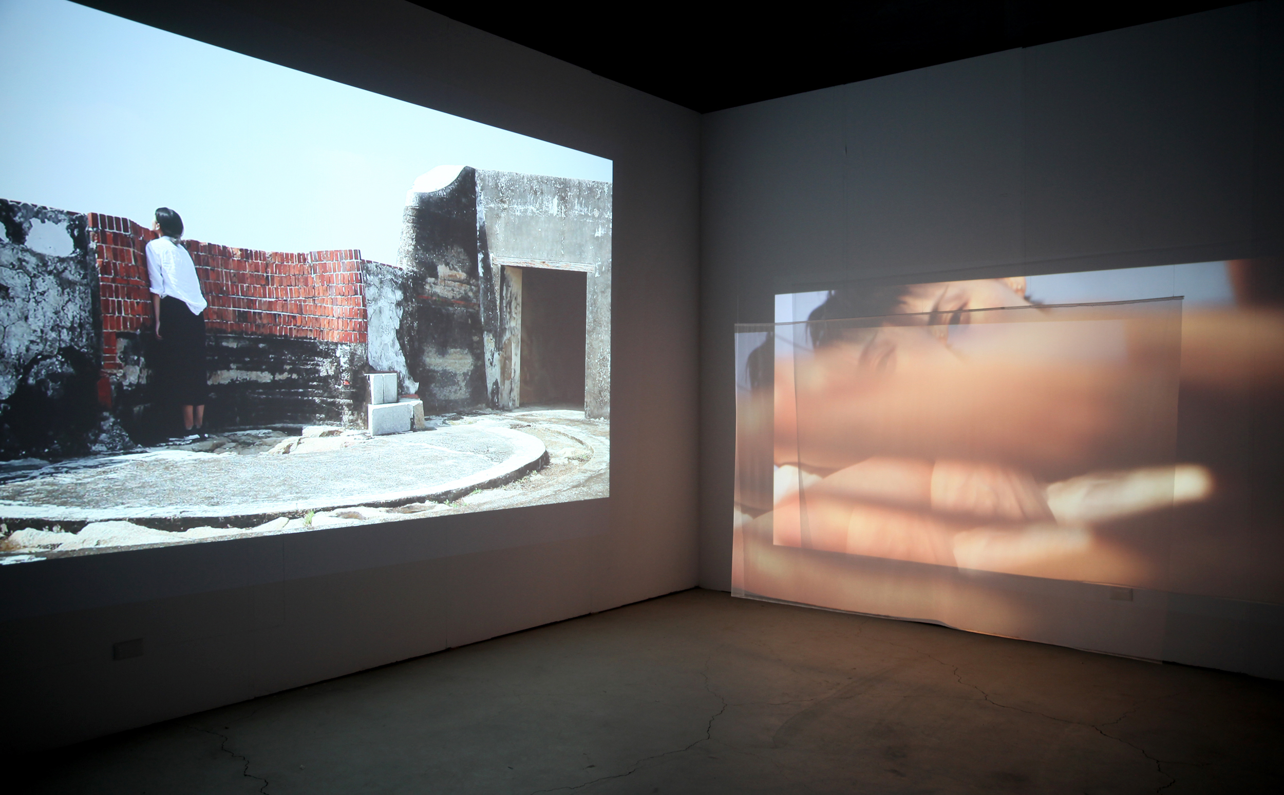 Anchor and A Loose Thread — 錨,和懸絲  2019 Two-channel video installation Dimensions variable  Dancers: Tso Han-Jie 左涵潔 and Mimi Chang 張心瑜 Sound Design: Supina Bytol and Conor O'Hanlon  Installation view at Young Art Space, Pier 2 Art Center   This project was created during an artist residency at Pier 2 Art Center, Kaohsiung, Taiwan  Supported by Pier 2 Art Center, Bureau of Cultural Affairs, Kaohsiung City Government and Ministry of Culture (Taiwan)     To remember is to have an anchor for your belonging.  Anchor and A Loose Thread  explores elements of memory, its condition within the body and its image when materialised. In collaboration with dancers Tso Han Jie and Mimi Chang, Nikki Lam's two-channel video examines the contradictory and entangled relationships between memories, the body and their records, both from within and through image documentation.   Anchor and A Loose Thread  continues the artist's research into post-colonial hybridity through personal and collective memories. The work describes an exchange of memories between artist Nikki Lam and dancers Tso Han Jie and Mimi Chang. Lam drew on her personal histories of a multi-faceted identity (Hong Kong / Australian), and her ongoing investigations into the concept of belonging and remembering. Using elements such as object, site and poetry as provocations, Tso and Chang were invited to respond with movements from the past, reimagined, as well as gestures developed then and there, improvised.  Through rigorous translations at every part of the process—from English to Cantonese to Chinese, Lam is particularly interested in the untranslatable details. Repeatedly framing and re-framing Tso and Chang's movements, either through shooting or editing, fragments of their memories are constantly re-considered. Between the artists, this process of materialising memory become a group exercise of recordings and translations. Of these records, historical sites such as Cijin Fort and Zongye stood quietly in reference t