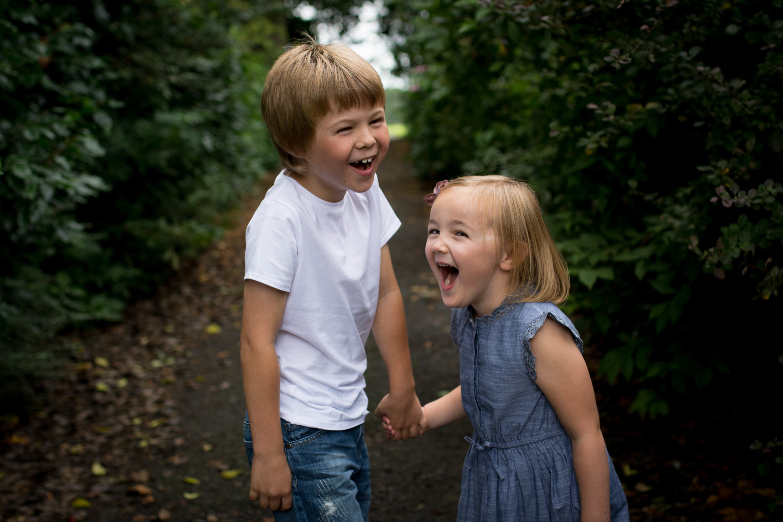 little girl laughing with brother outdoor photo shoot in barshaw park paisley near Glasgow